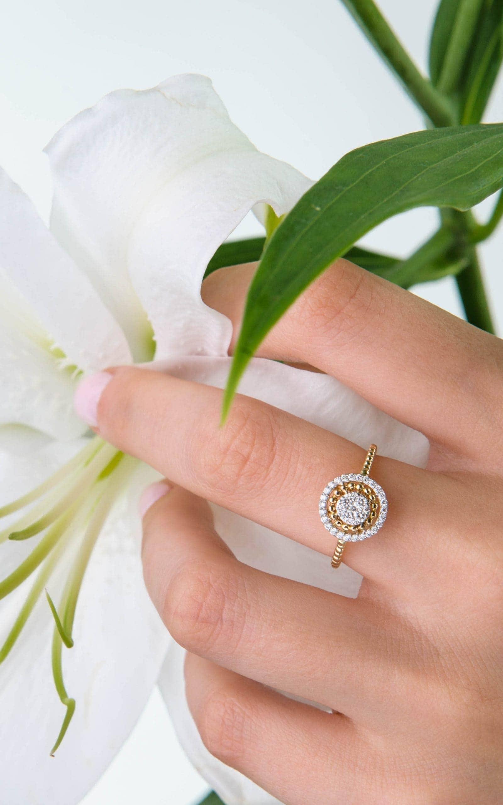 Modelka prezentuje na dłoni złoty pierścionek z brylantami trzymając biały kwiat.