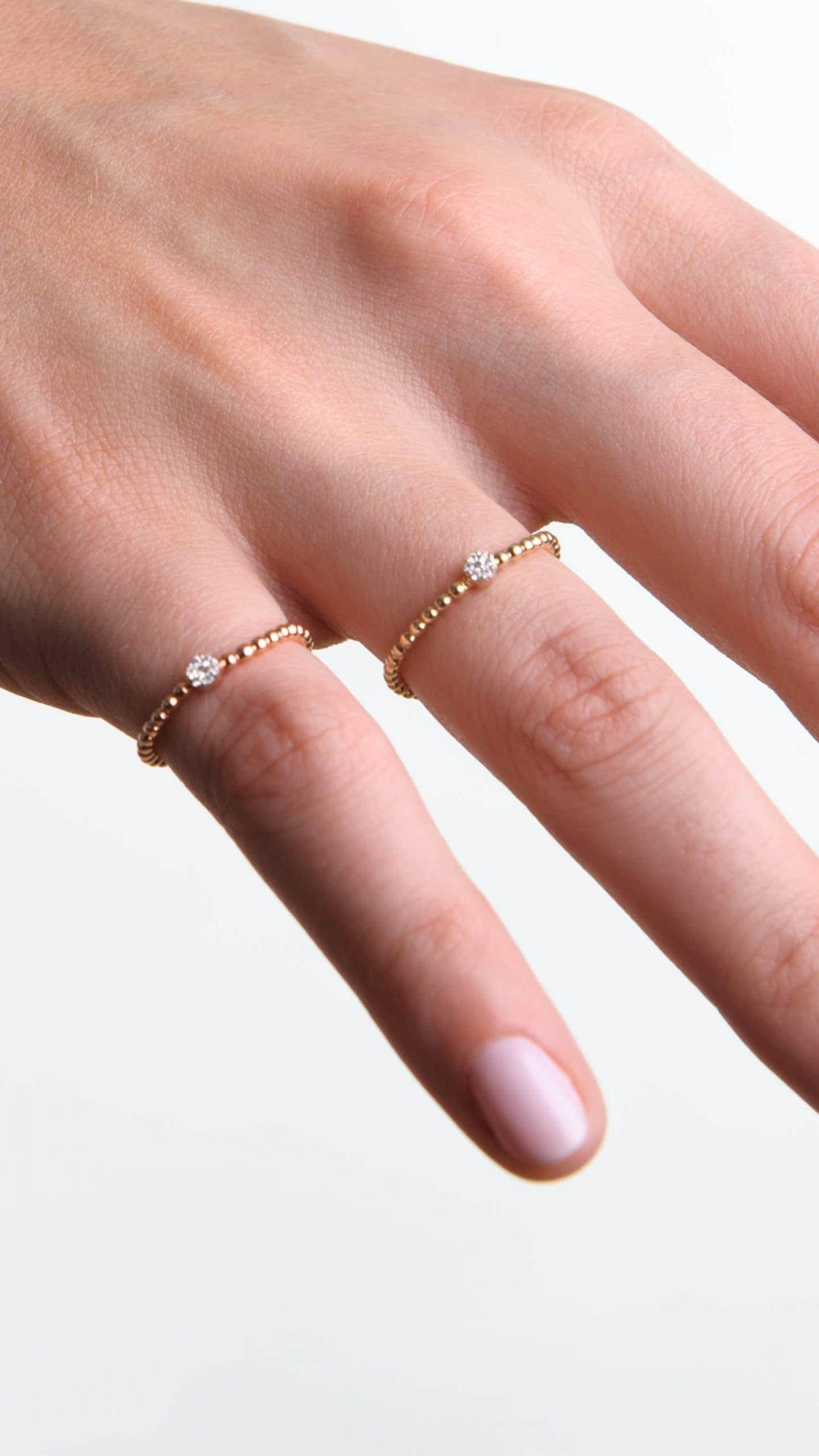 Modelka prezentuje na dłoni zestaw złotych pierścionków. Jeden jest wykonany z różowego złota, drugi z żółtego, oba wysadzane są naturalnymi diamentami.