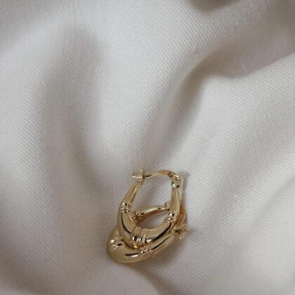 Delikatne złote kolczyki na jasnym materiale