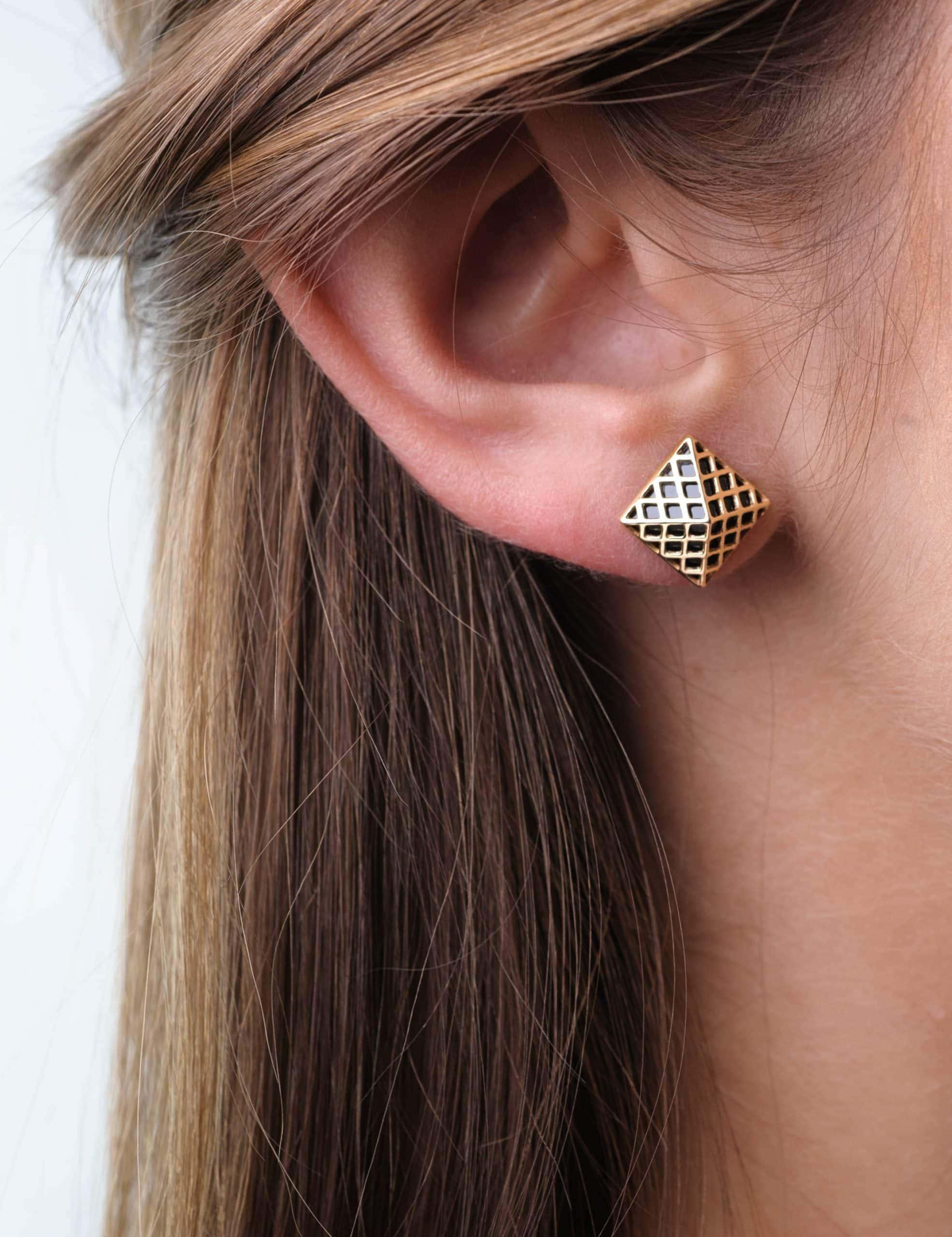 Modelka prezentuje na uchu złote kolczyki z onyksem w formie nietypowych piramidek.