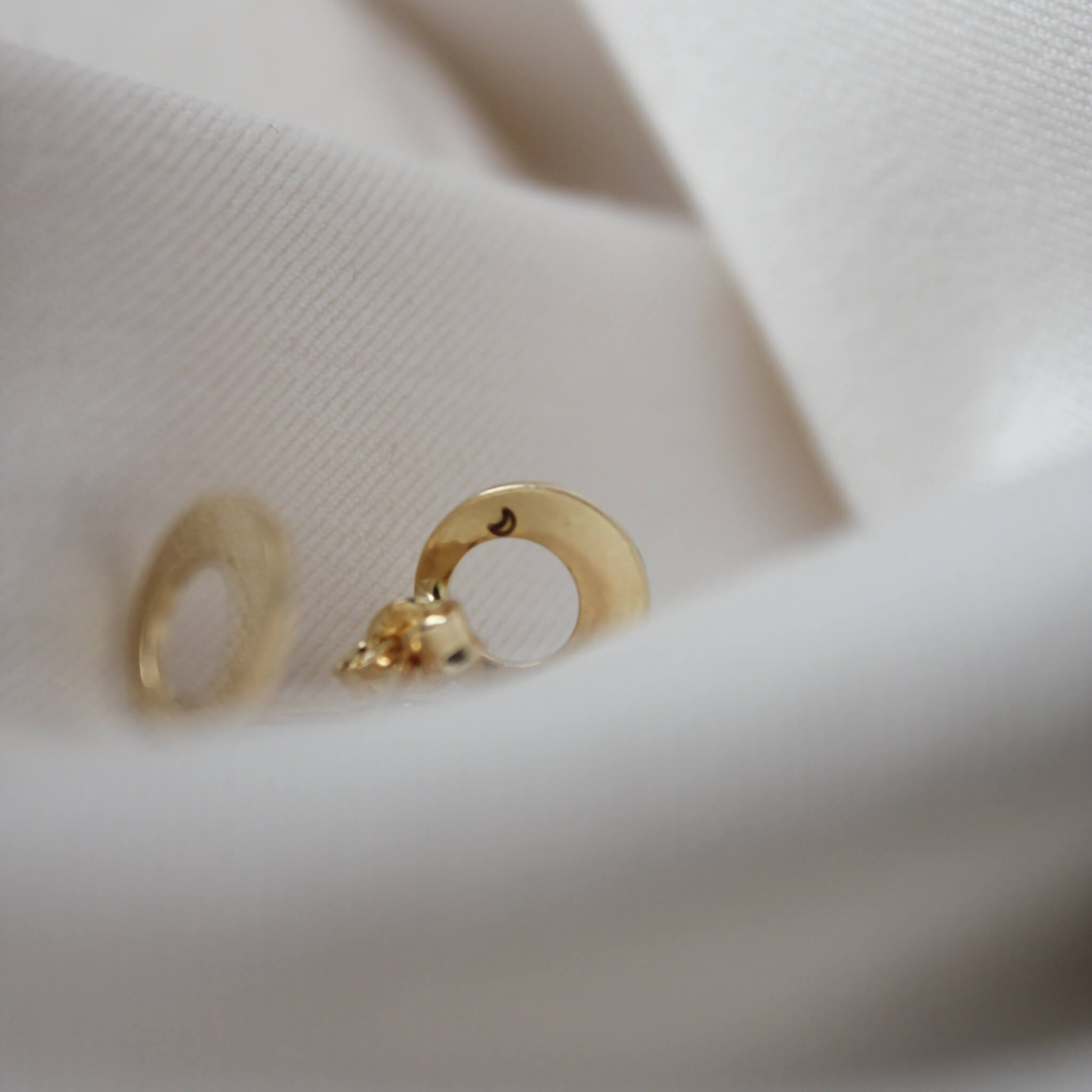 Minimalistyczne złote kolczyki na jasnym materiale z wygrawerowanym Księżycem.