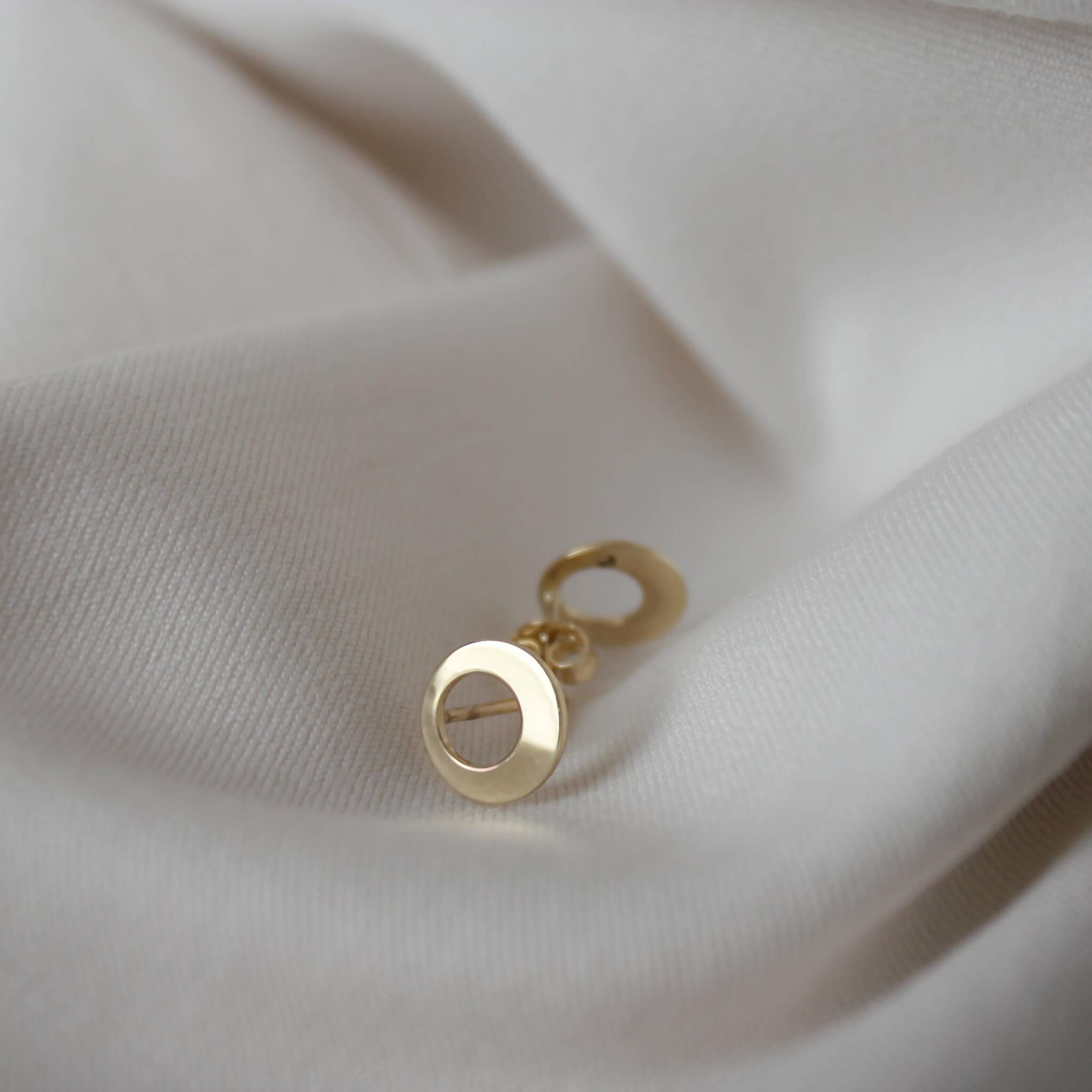 Delikatne złote kolczyki na jasnym materiale.