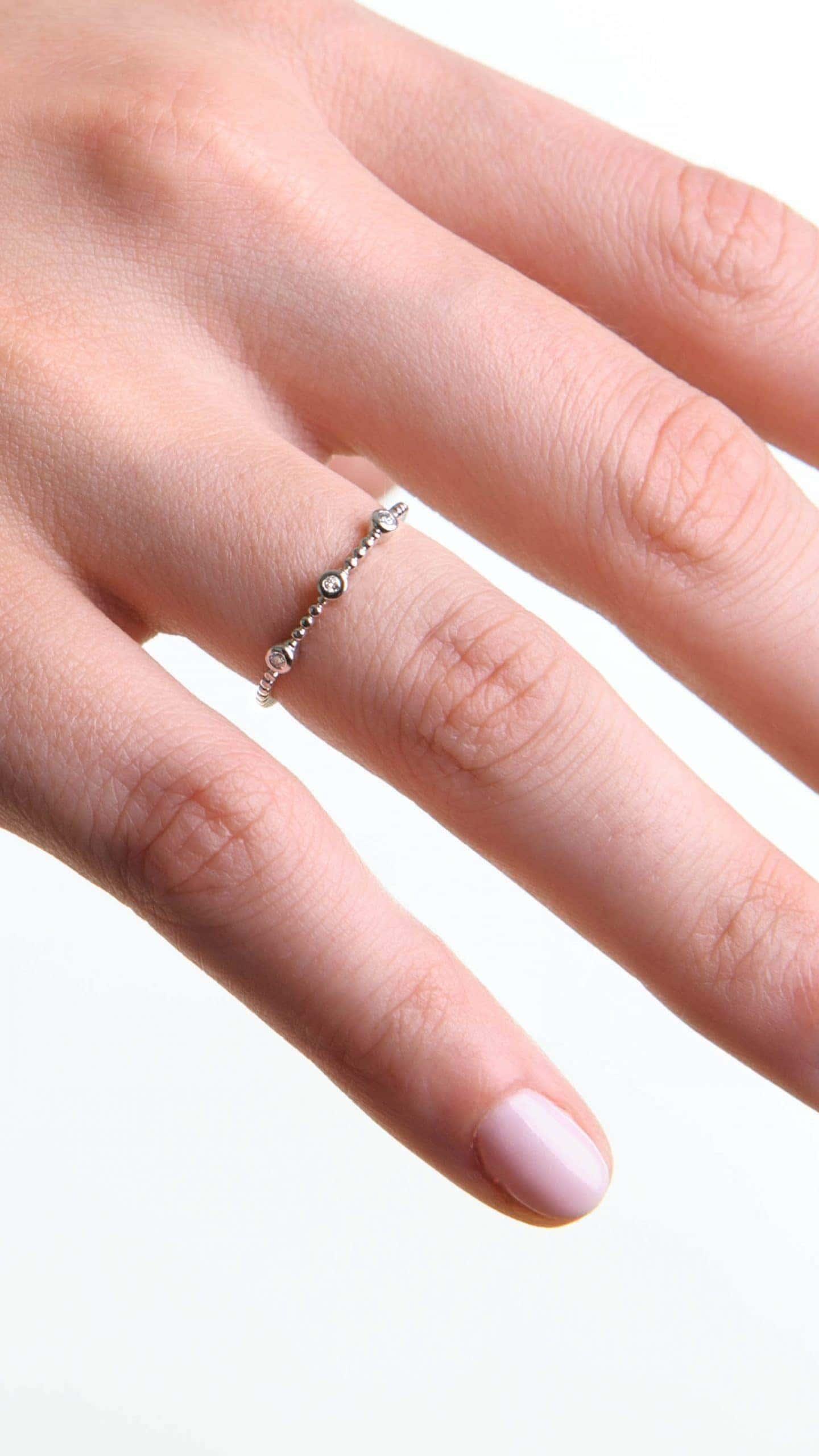 Modelka prezentuje na dłoni złoty pierścionek z białego złota z diamentami