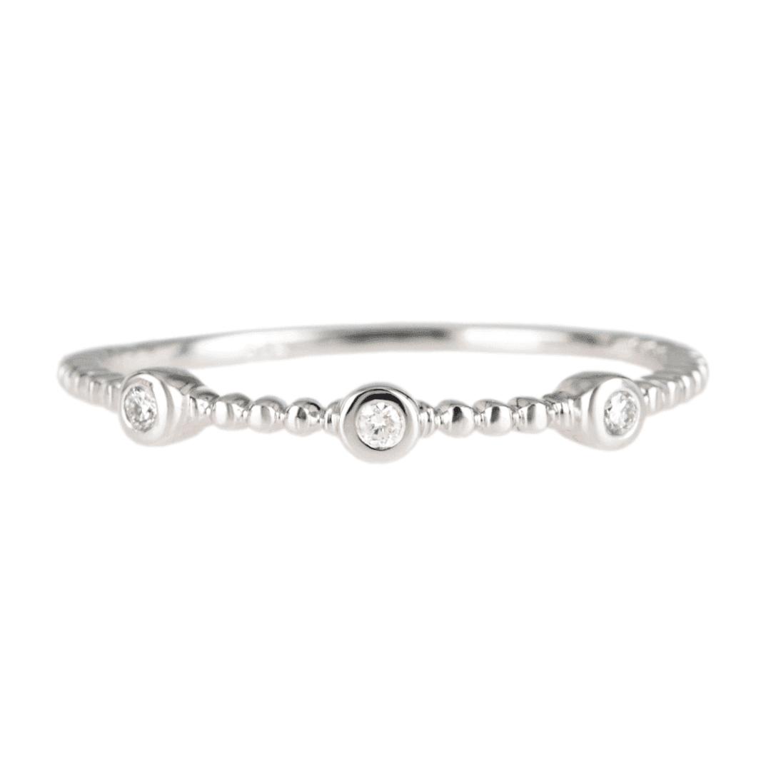 Delikatny pierścionek z białego złota z brylantami na jasnym tle.