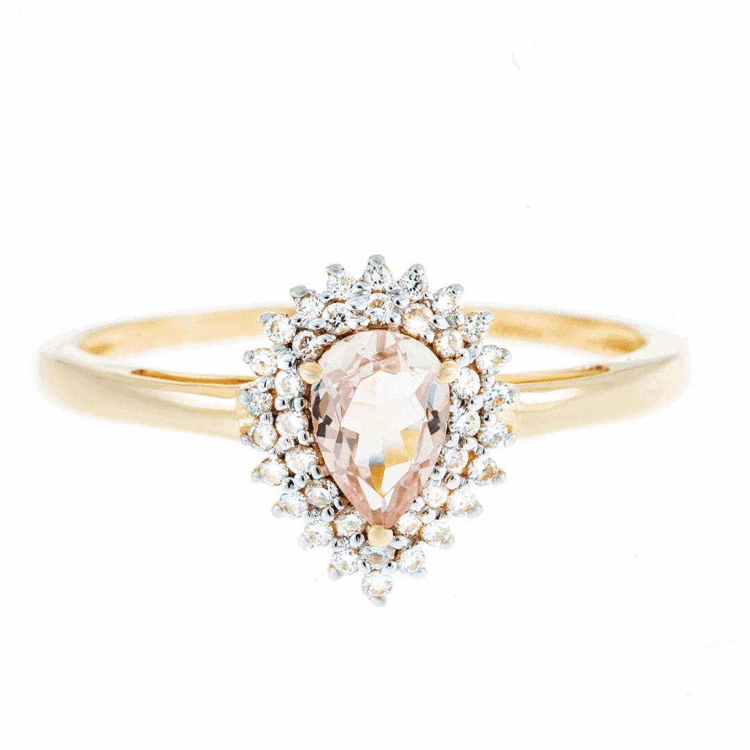Połyskujący złoty pierścionek z morgatem i diamentami na jasnym tle.