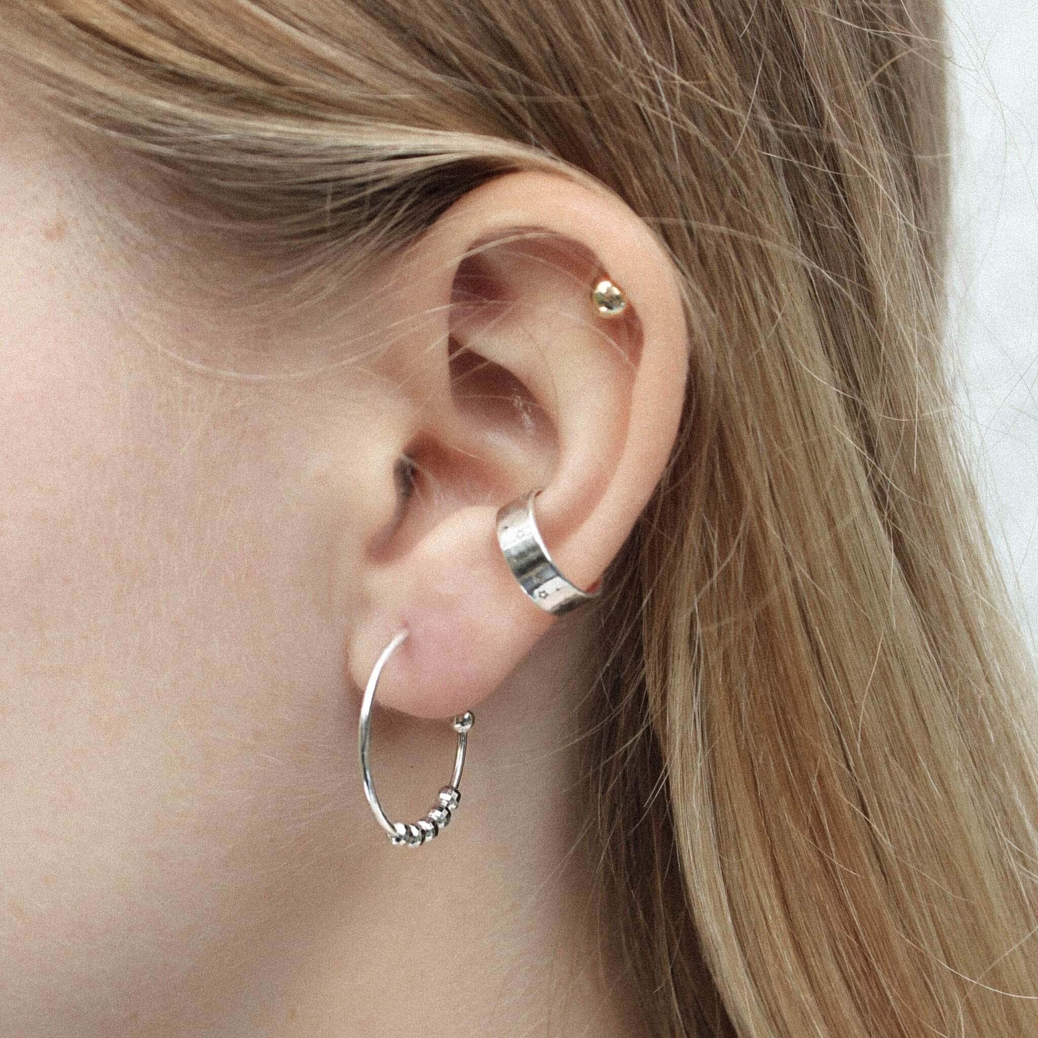 Modelka prezentuje zestaw srebrnej biżuterii. Ma na uchu srebrne kolczyki koła i srebrną nausznicę.