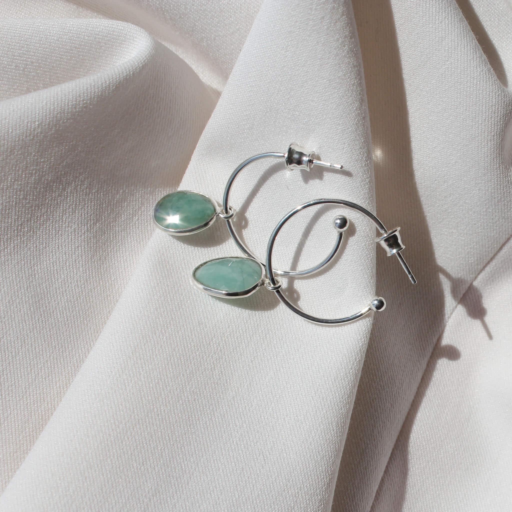 Srebrne kolczyki z zawieszką w formie naturalnych szmaragdów na jasnym materiale