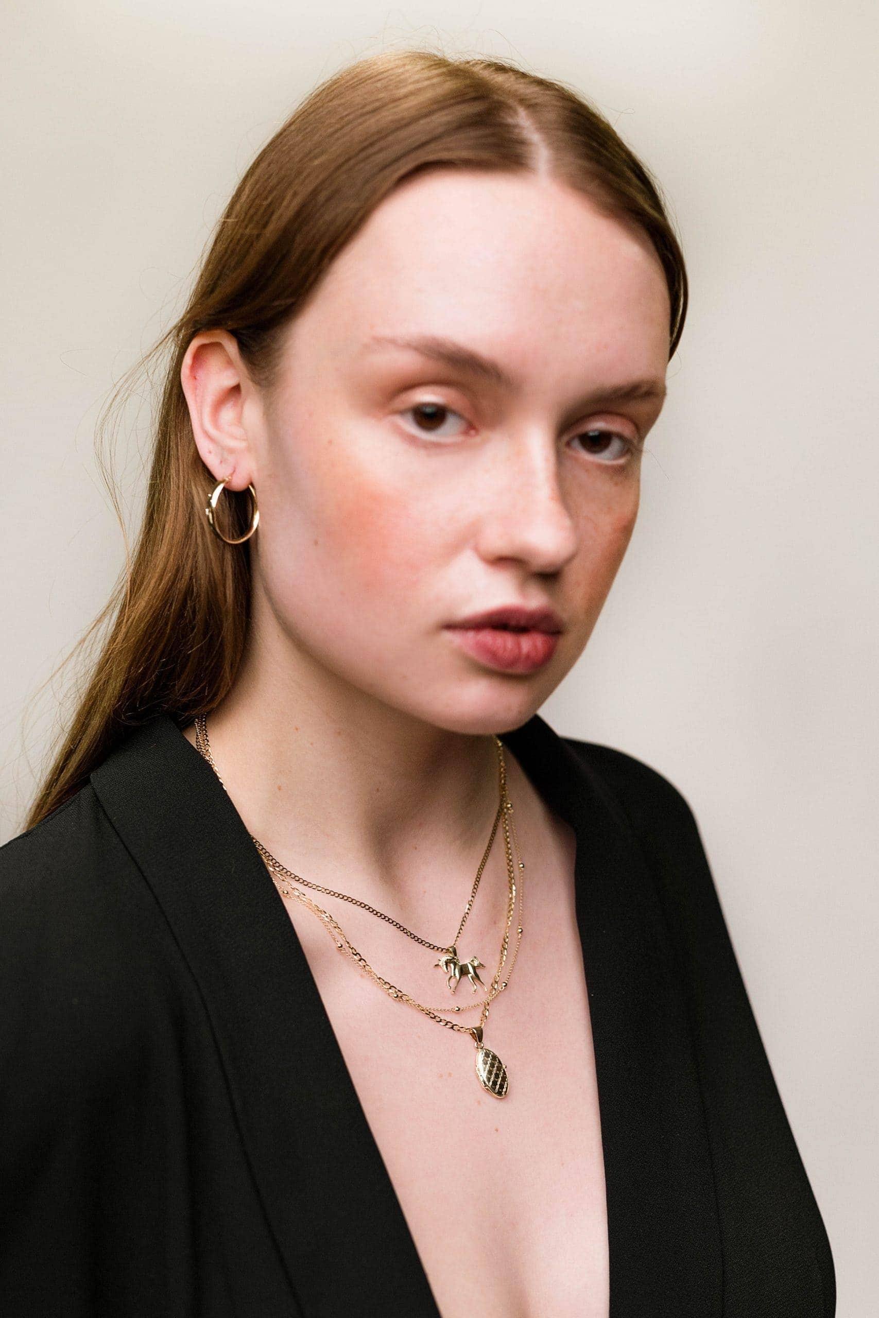 Modelka prezentuje zestaw złotej biżuterii: kolczyki koła, naszyjniki i sekretnik na fotografię.