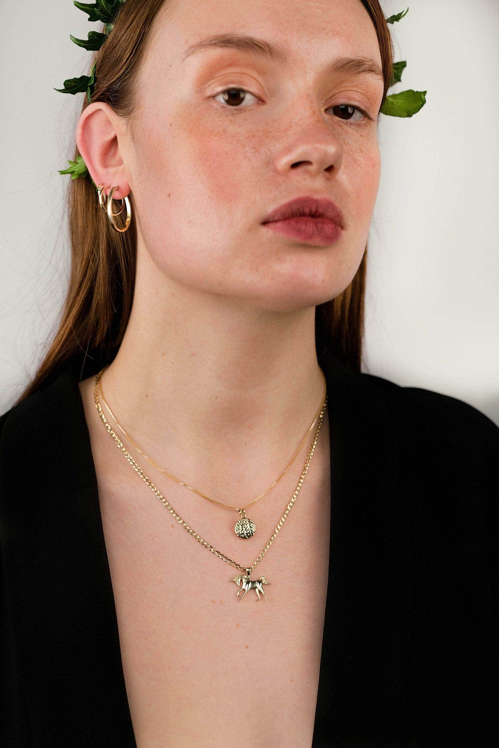 Modelka ma na sobie zestaw złotej biżuterii: kolczyki koła, naszyjnik, złotą zawieszkę