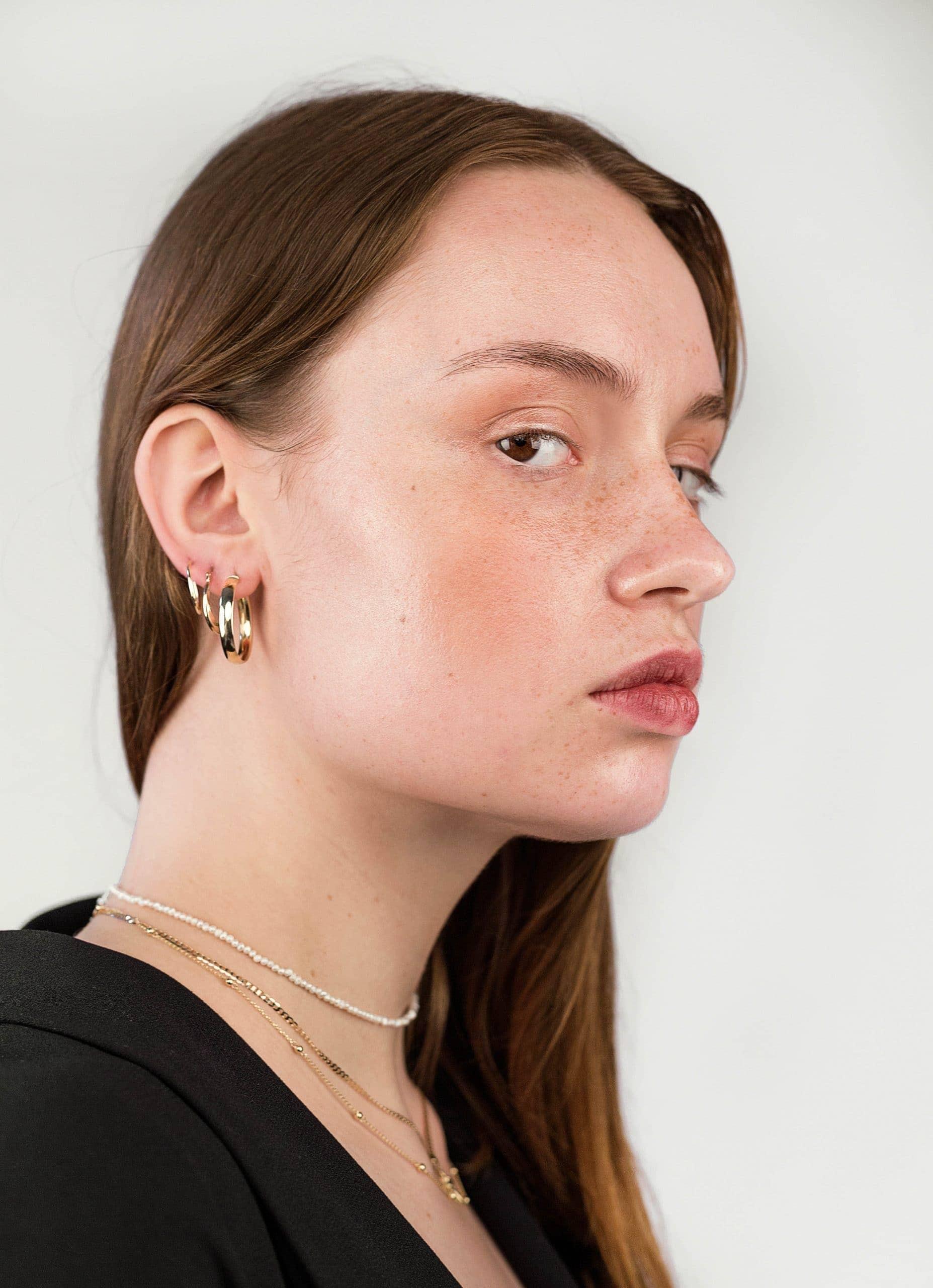 Modelka pprezentująca złotą biżuterię i choker z pereł