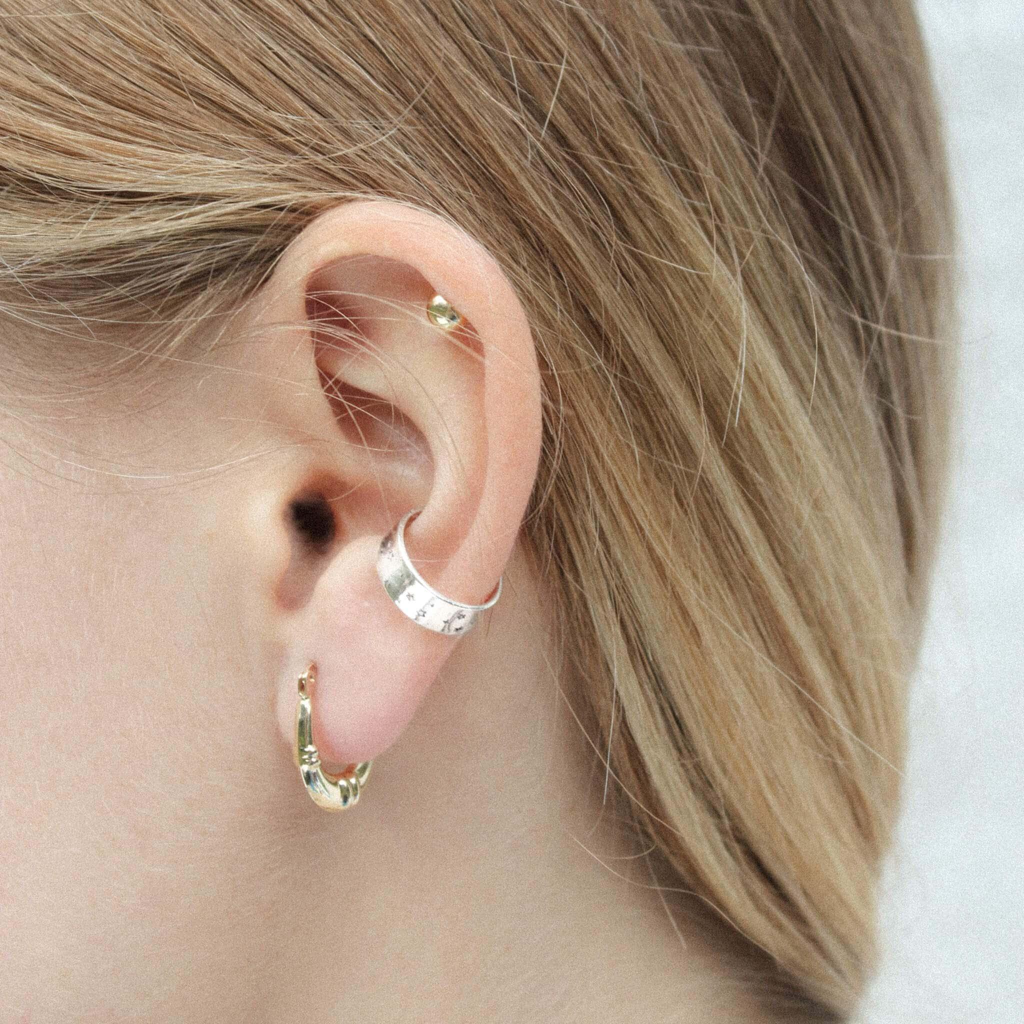 Modelka prezentuje złotą i srebrną biżuterię: klasyczne kolczyki i srebrną nausznicę