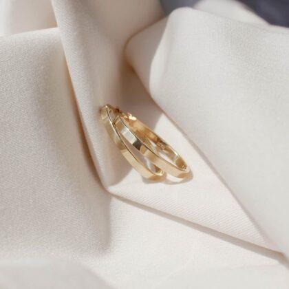 Złote kolczyki o owalnym kształcie na białym materiale.
