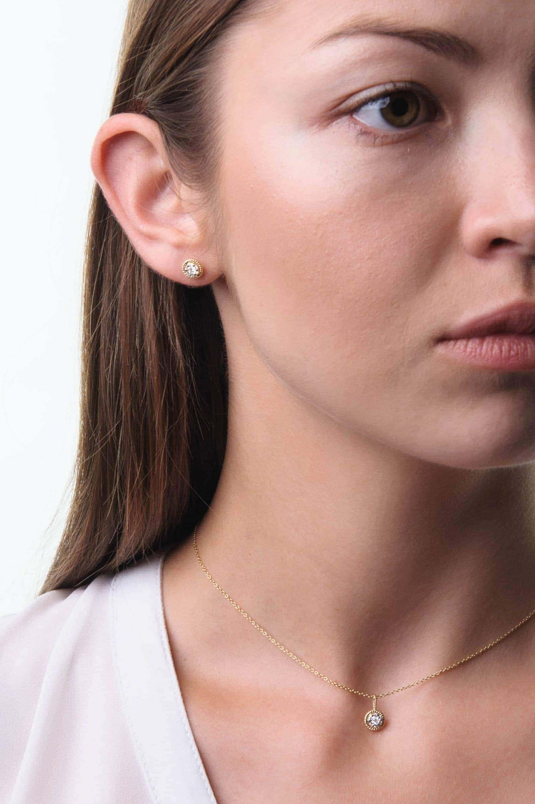 Modelka o ciemnym włosach prezentuje zestaw złotej biżuterii z diamentami.