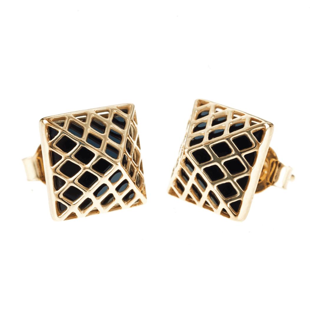 Złote kolczyki z onyksem w formie piramidek na jasnym tle.