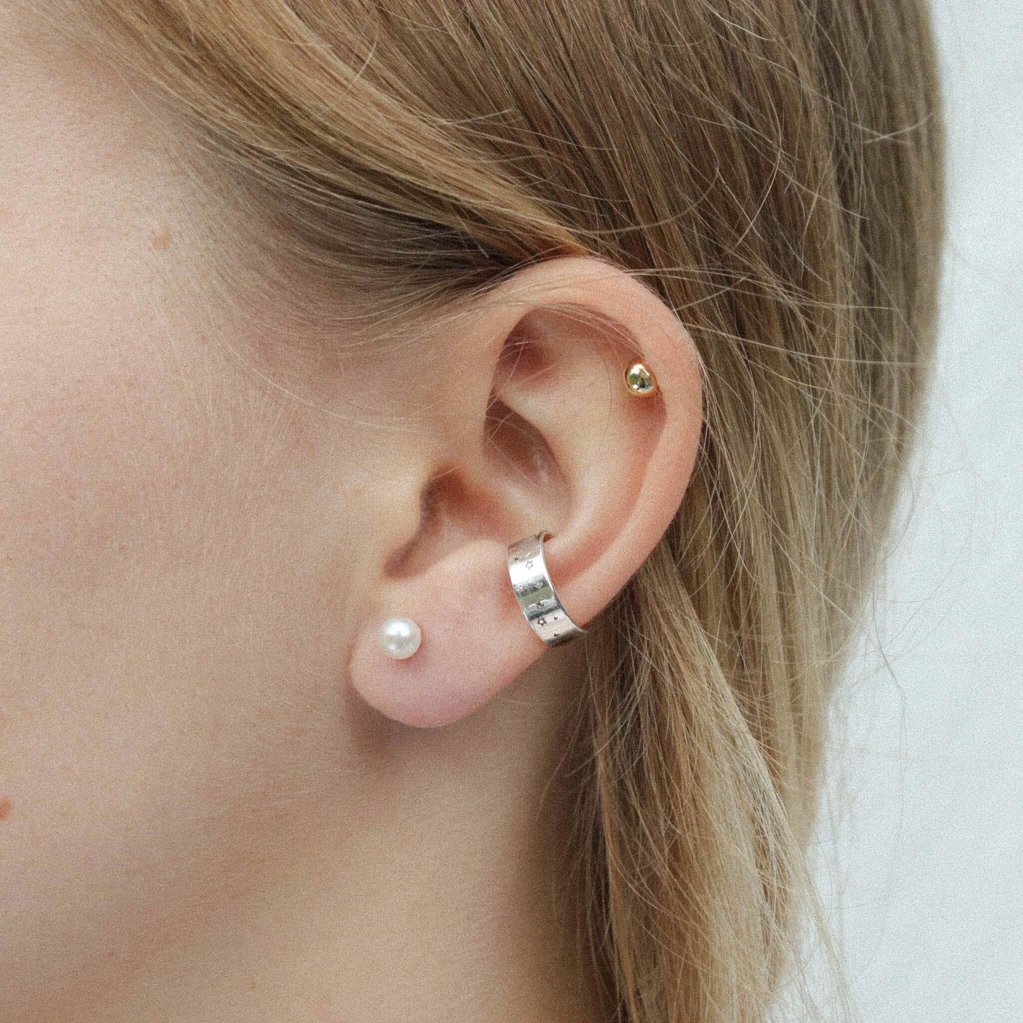 Modelka prezentuje złote kolczyki z perłami