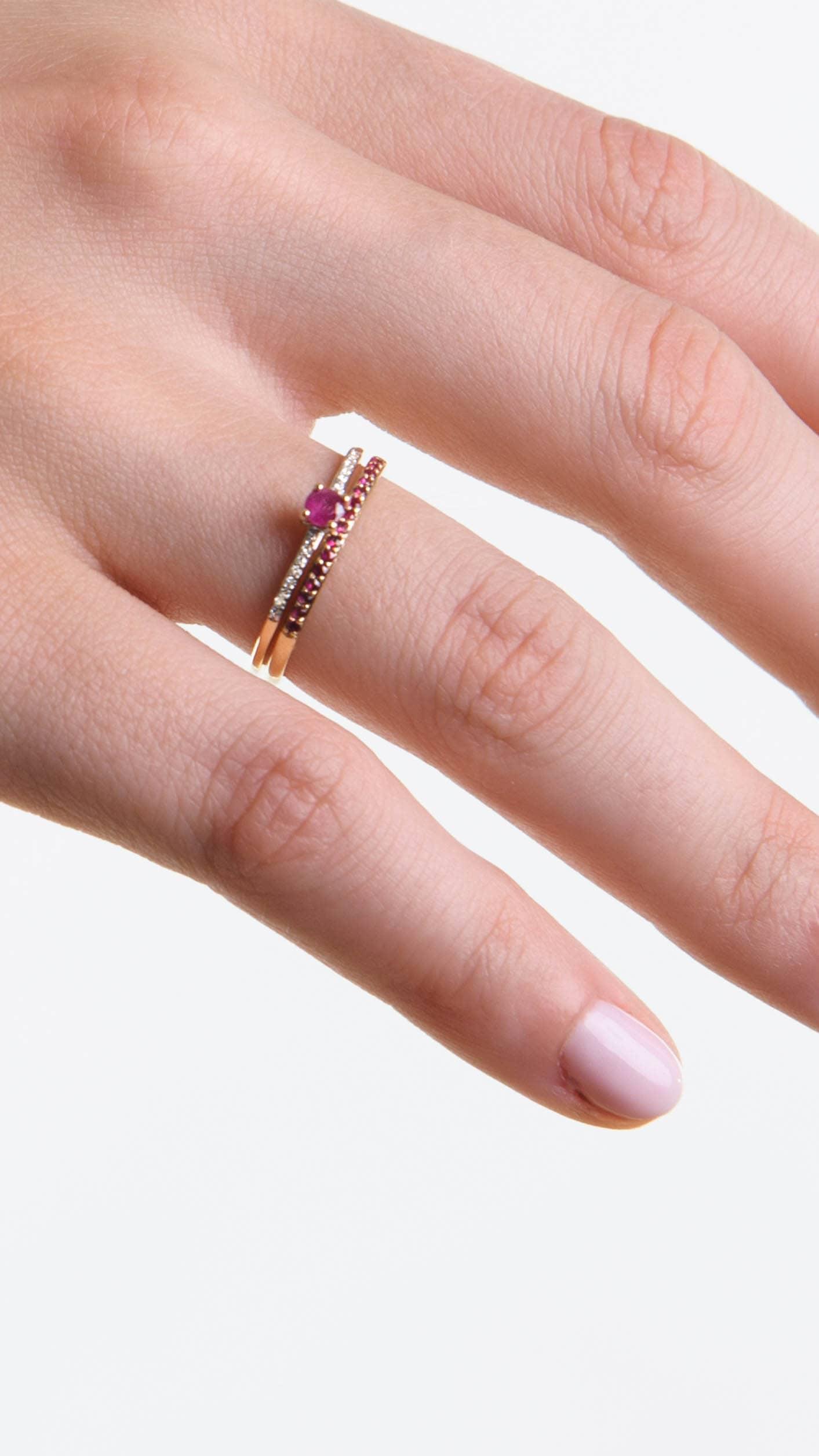 Modelka prezentuje na dłoni zestaw złotych pierścionków z kamieniami szlachetnymi: rubinami i diamentami.