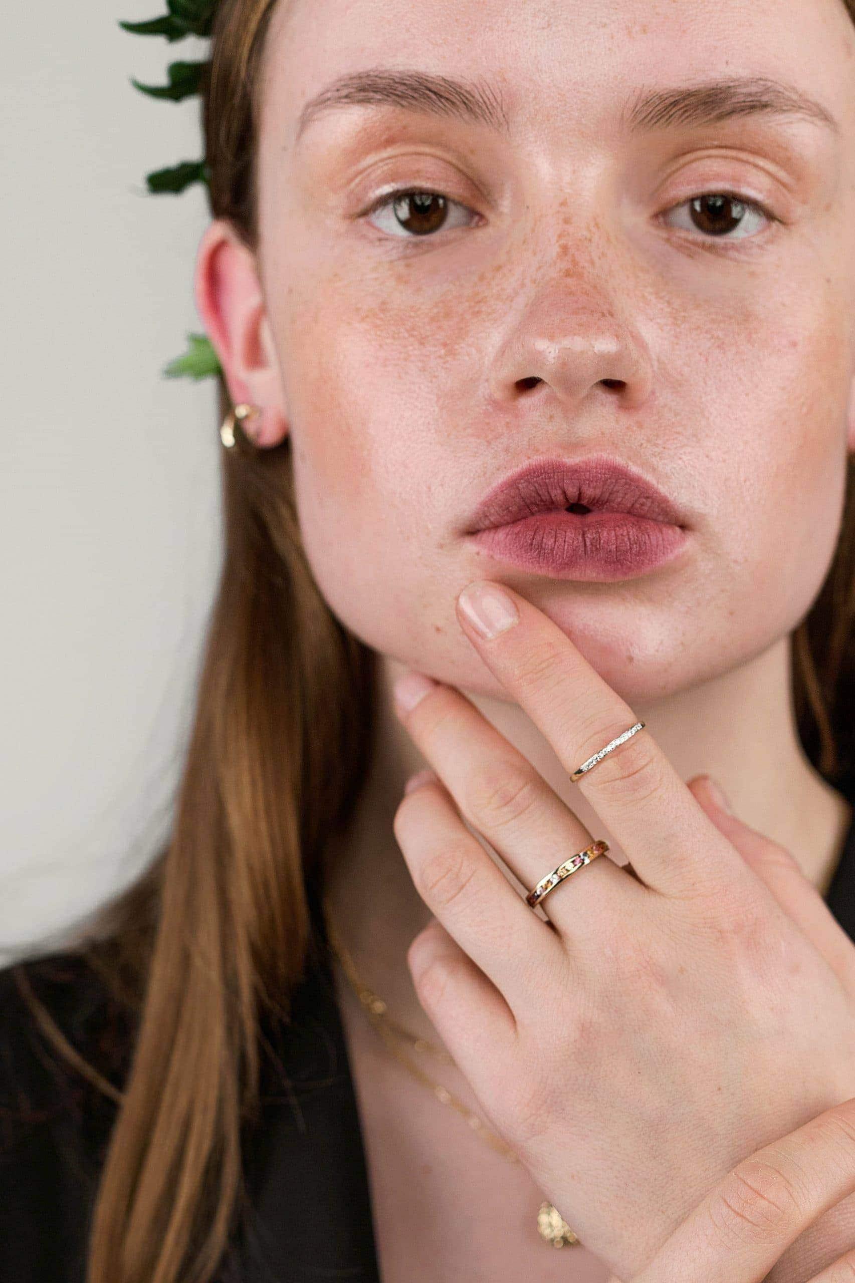 Modelka prezentuje na dłoniach złote pierścionki z kamieniami szlachetnymi.