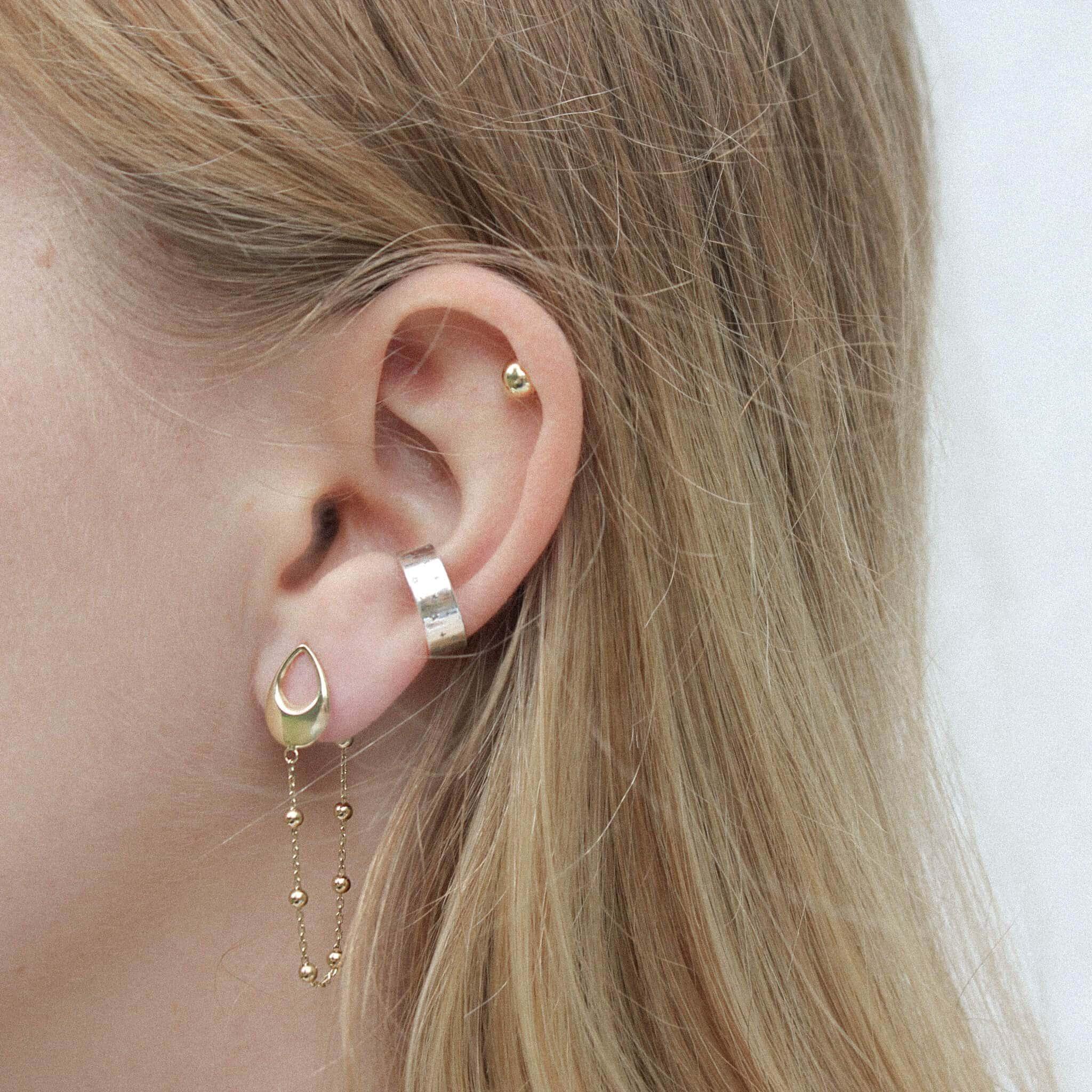 Modelka prezentuje delikatne złote kolczyki i srebrną nausznice.