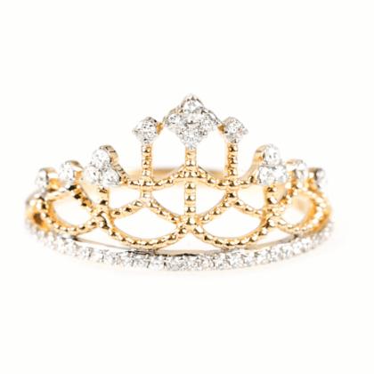 Złoty pierścionek z diamentami w formie korony na jasnym tle