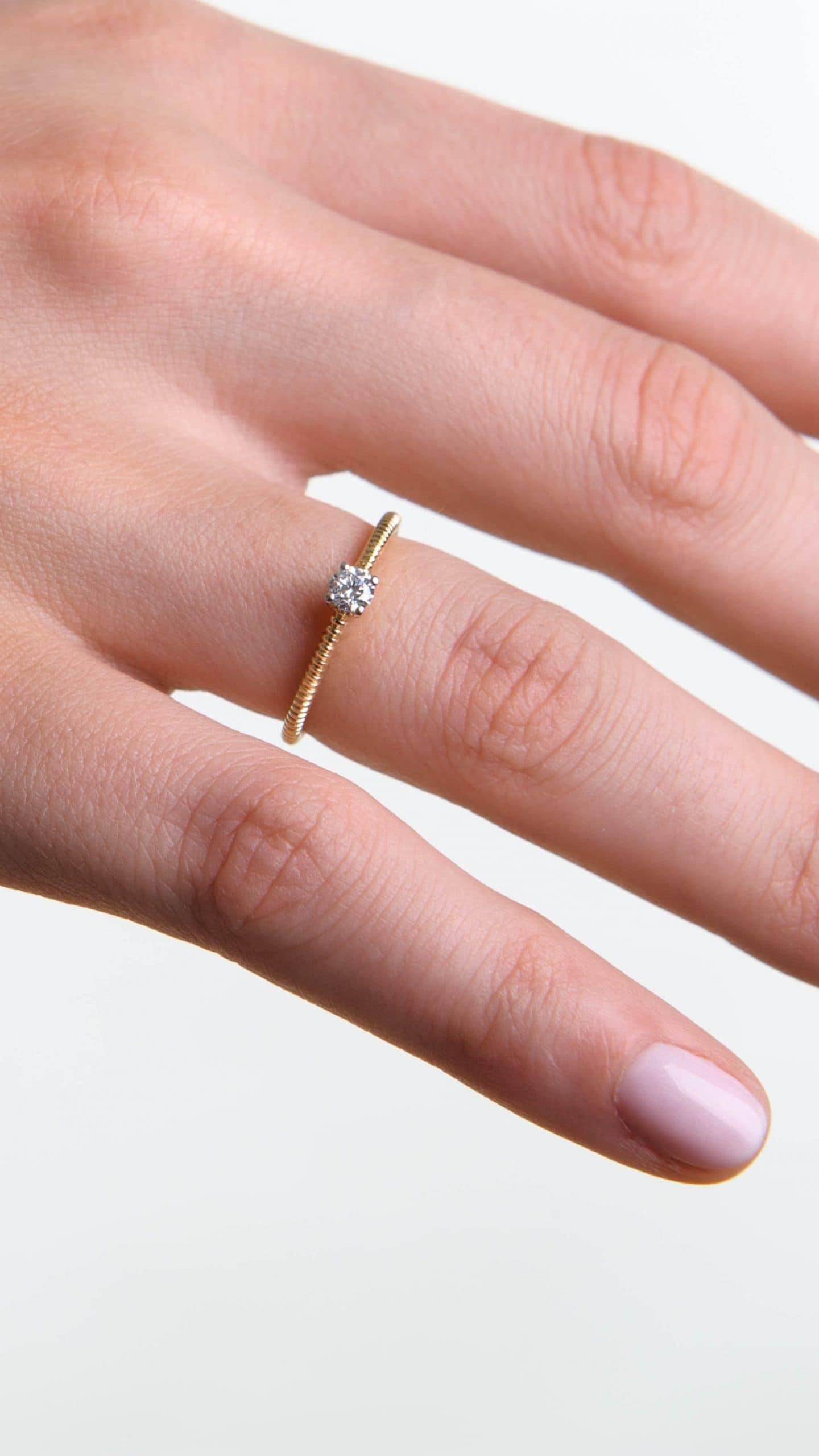 Modelka prezentuje na dłoni pierścionek z żółtego złota z centralnie osadzonym diamentem