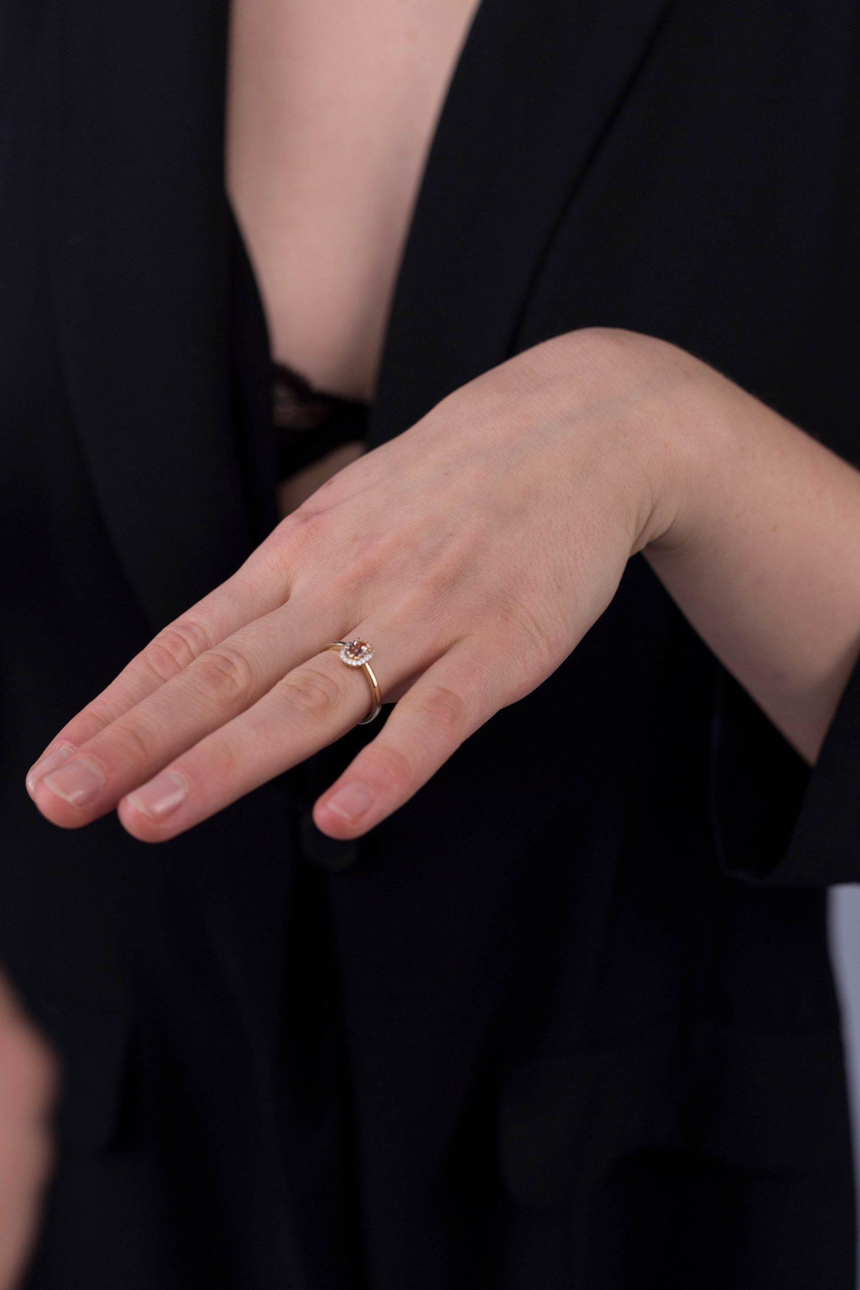 Modelka prezentuje na dłoni złoty pierścionek zaręczynowy z morganitem i diamentami. Obrana jest na czarno.