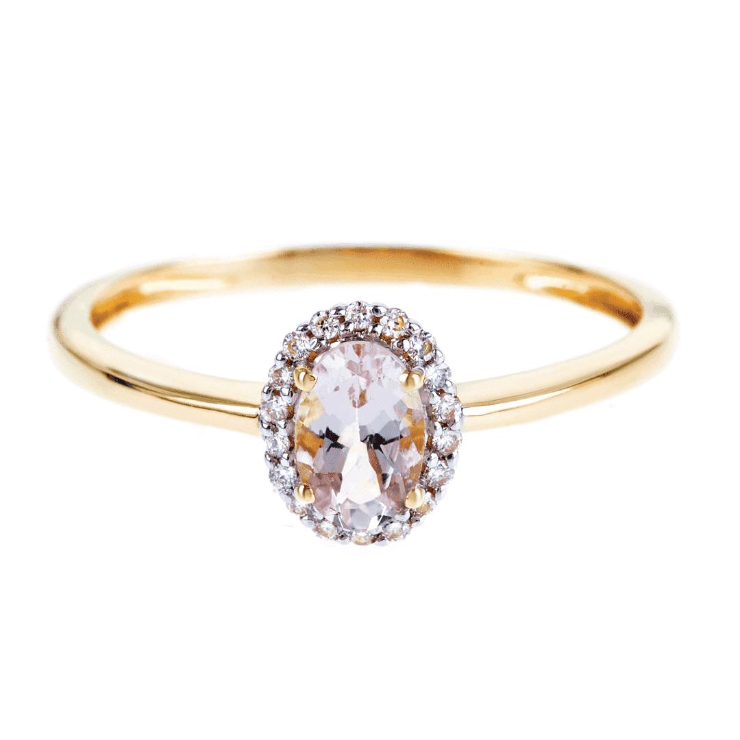 Subtelnie połyskujący złoty pierścionek z morganitem i diamentami na jasnym tle.