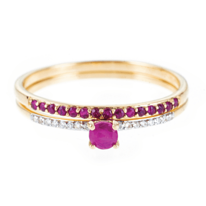 Złote pierścionki ułożone jeden na drugim wykonane ze złota z różowymi rubinami i białymi diamentami
