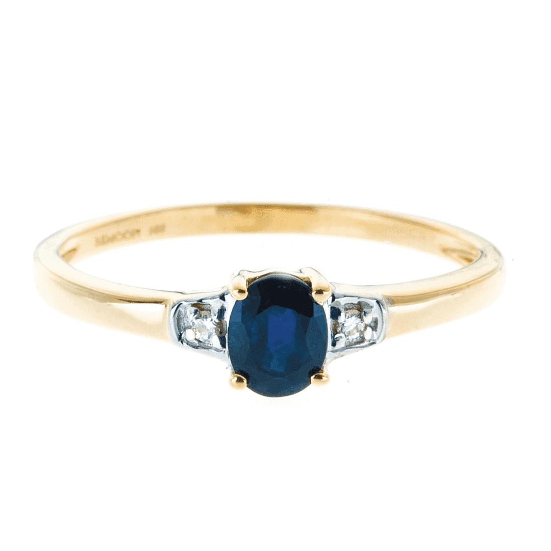 Pierścionek ze złota z błękitnym szafirem i naturalnymi brylantami po bokach.