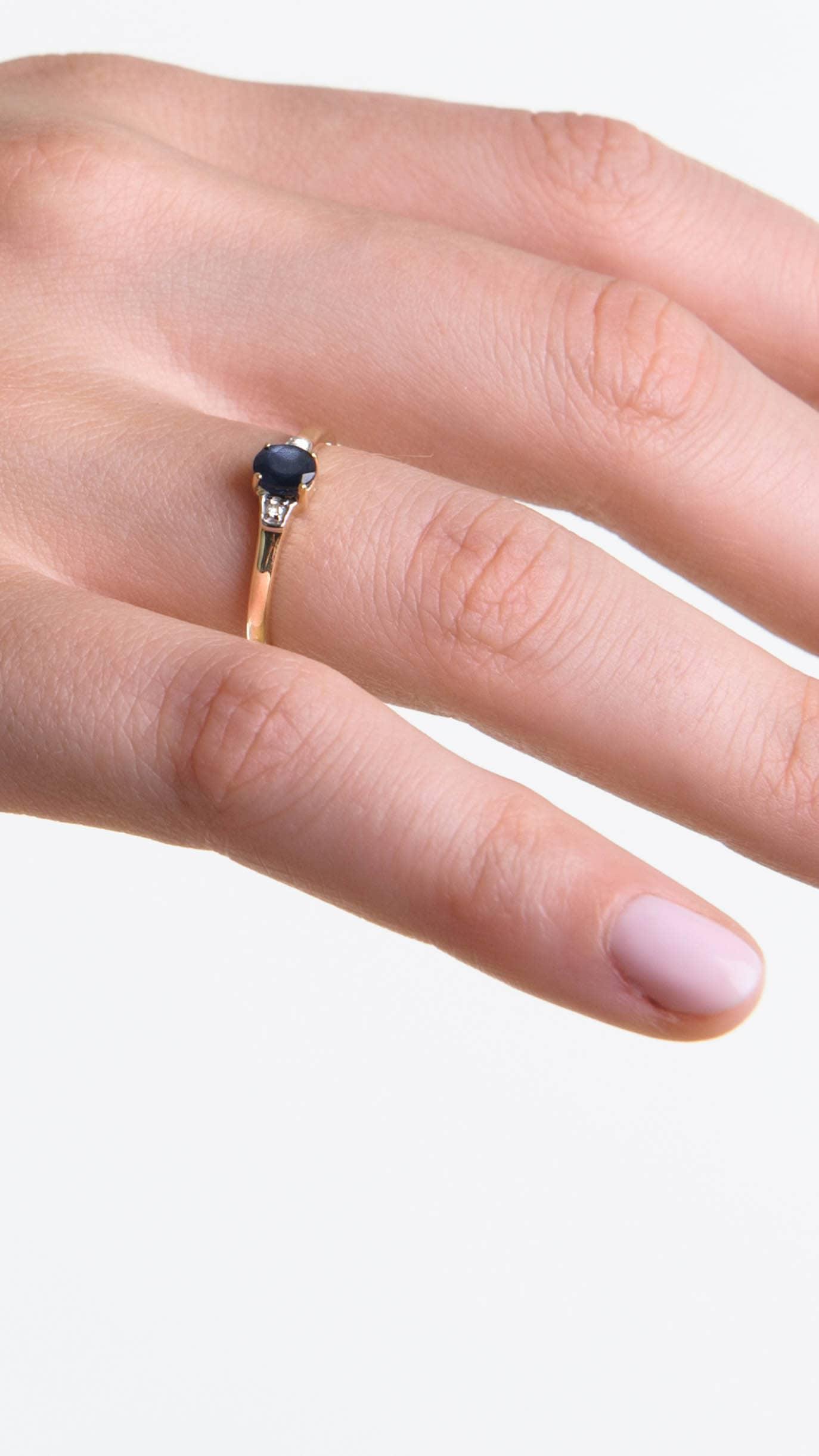Modelka prezentuje na dłoni złoty pierścionek z błękitnym szafirem i naturalnymi diamentami.