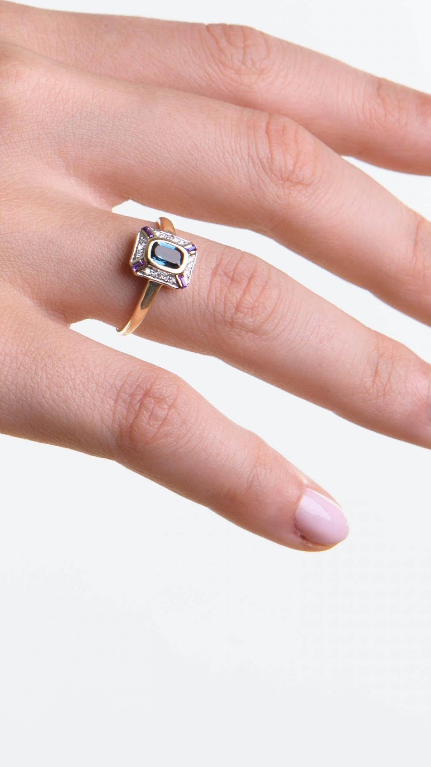 Modelka prezentuje na dłoni złoty pierścionek z błękitnym topazem i błyszczącymi diamentami.