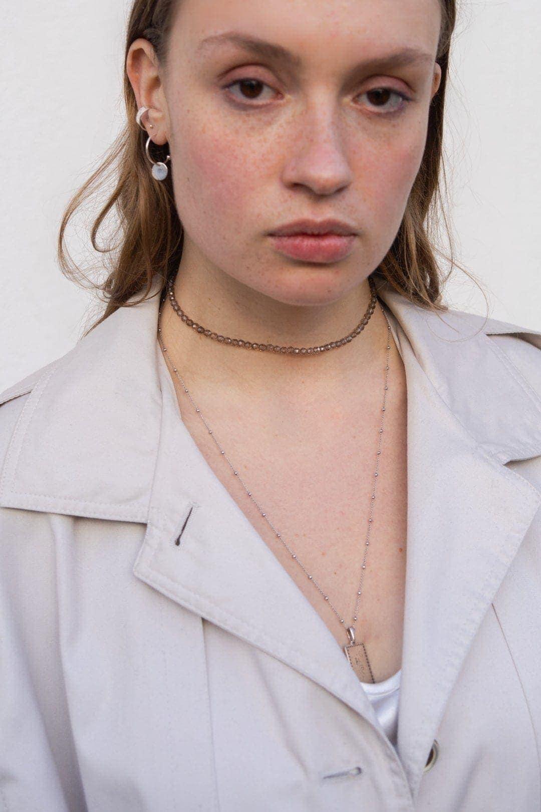 Modelka prezentuje zestaw biżuterii autorskiej: naszyjnik z grawerem, choker na szyje, nausznice i kolczyki koła z zawieszką.