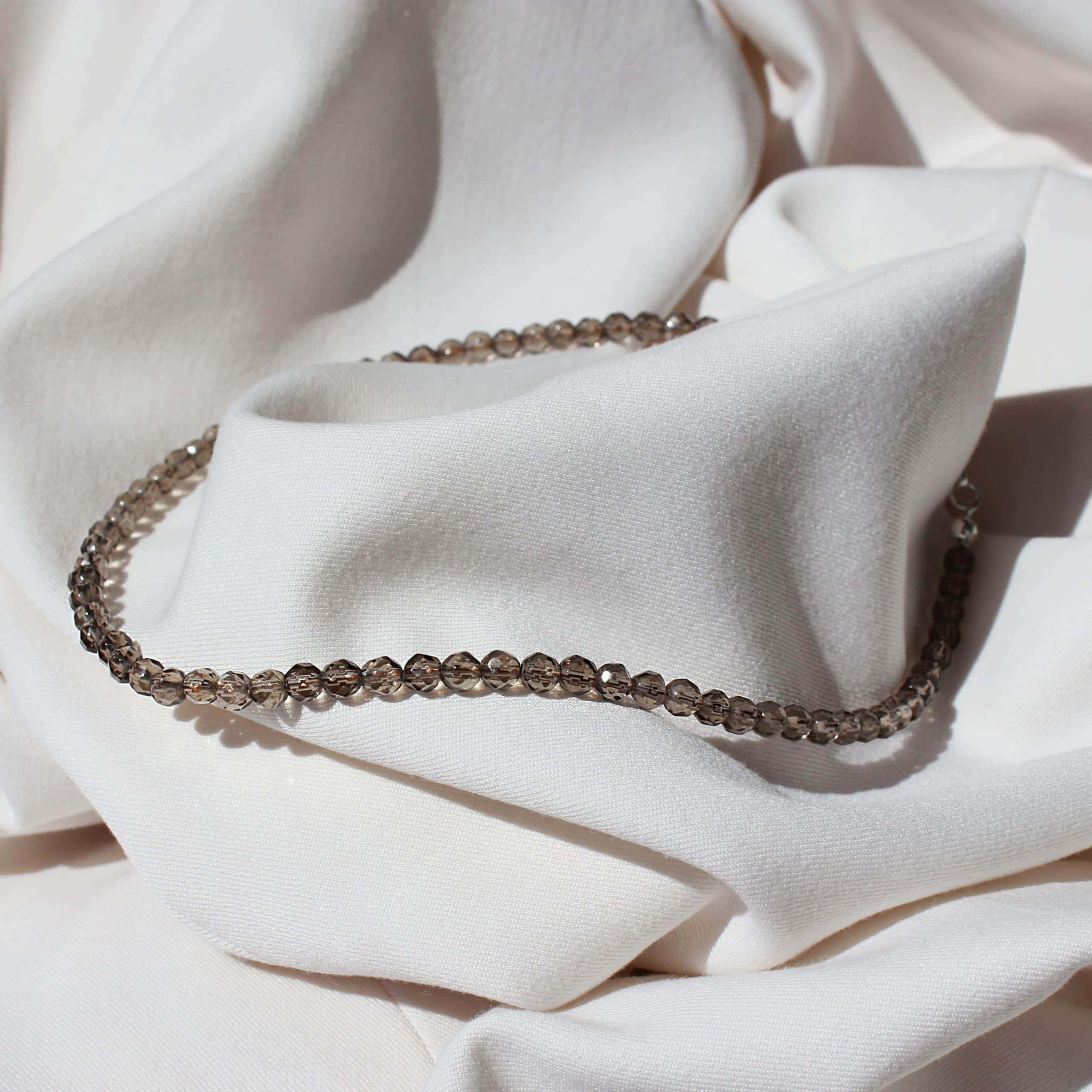 Brązowy choker na szyje z naturalnych kamieni szlachetnych na jasnym materiale.