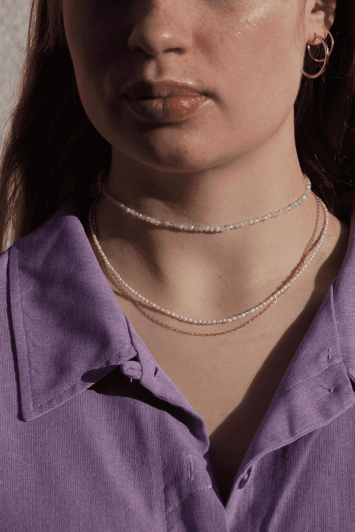 Modelka prezentuje naszyjnik z kamieniem i choker na szyję.