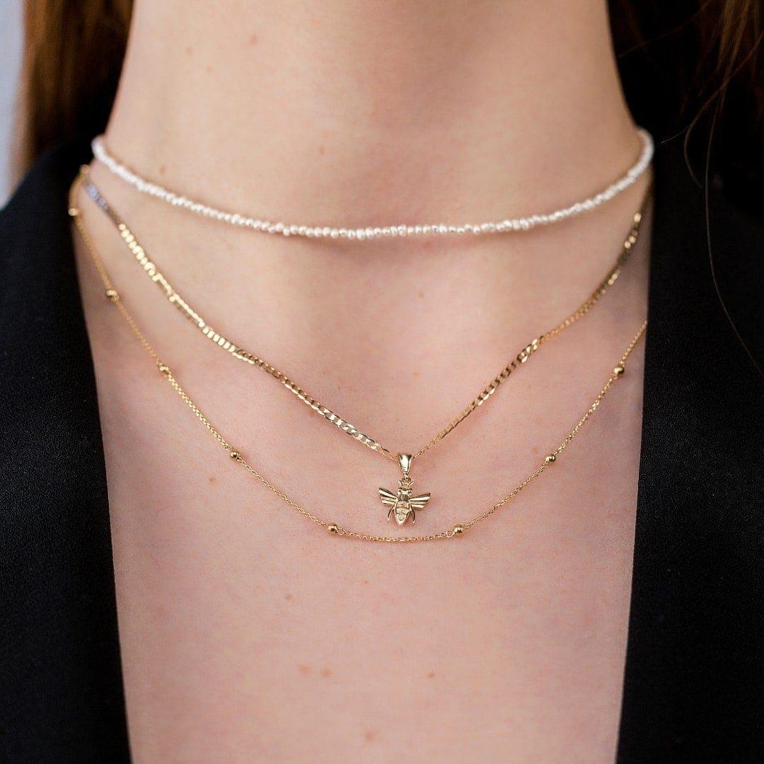 Modelka prezentuje na szyi zestaw złotej biżuterii. Ma zawieszkę pszczółkę, choker z pereł i złoty naszyjnik.