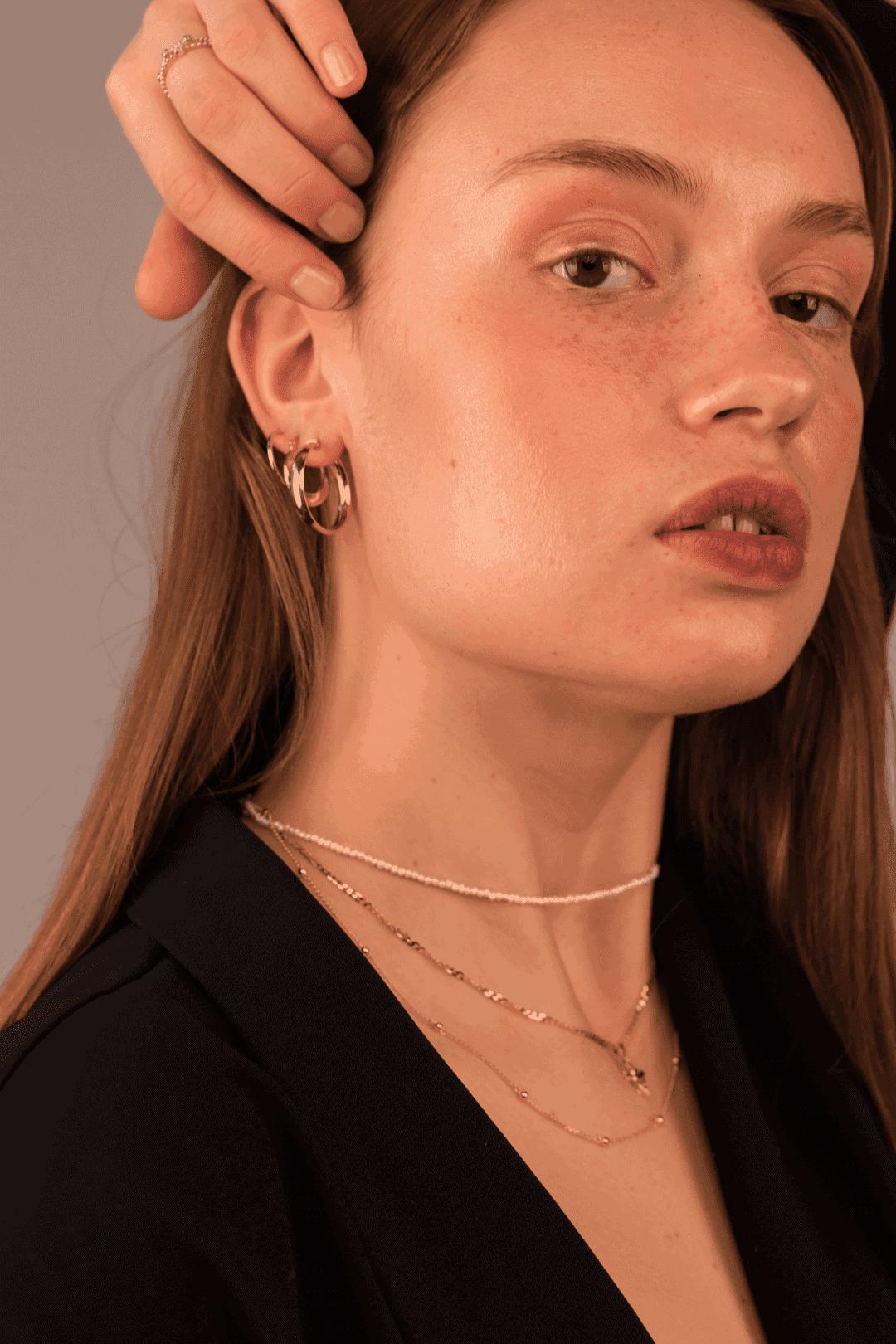 Modelka prezentuje zestaw złotej biżuterii i choker z pereł