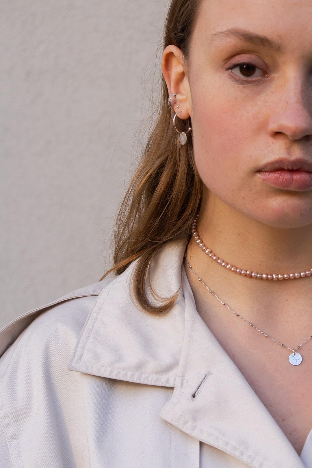 Modelka prezentuje na sobie choker z pereł i naszyjniik z grawerem BODY.