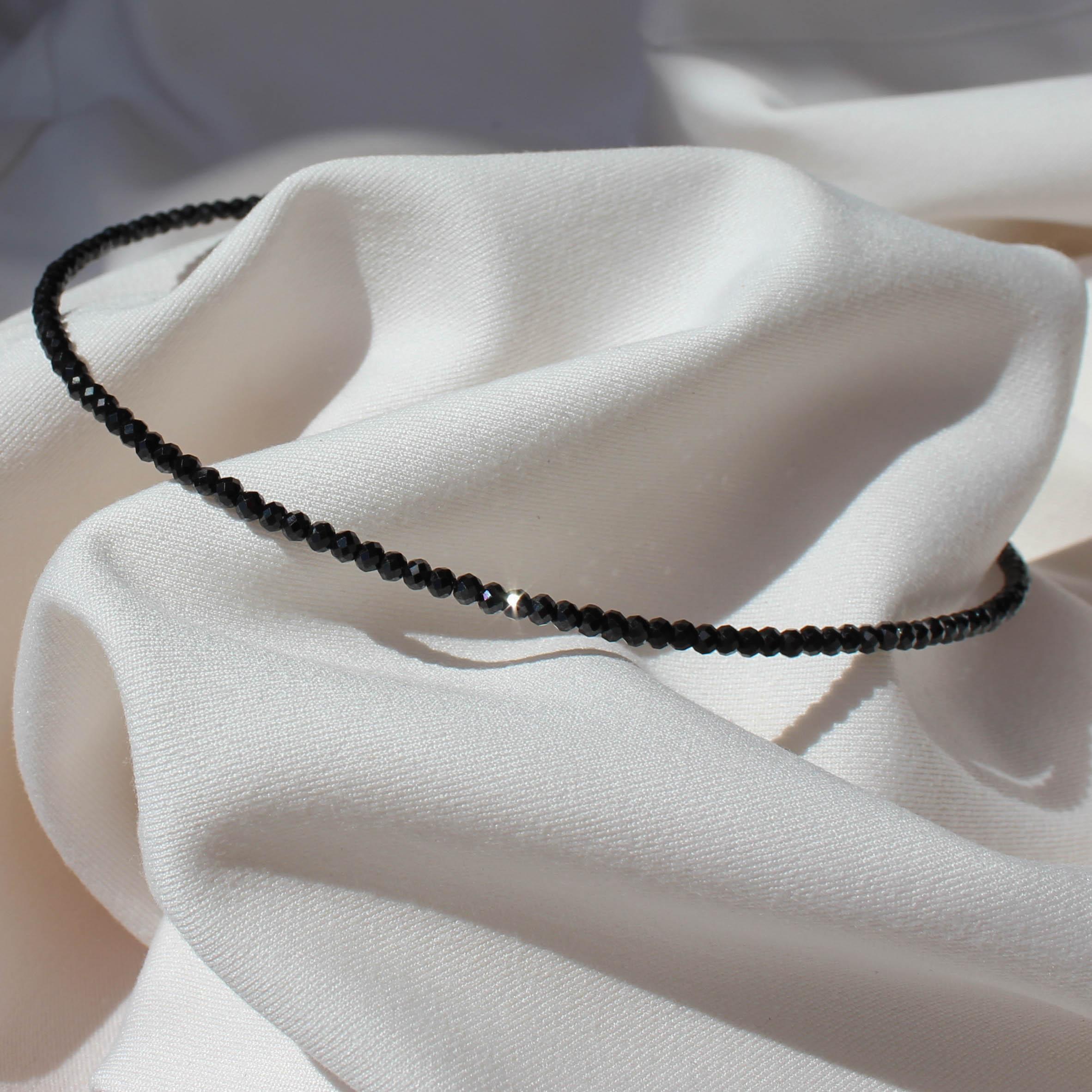 Czarny choker na szyje z połyskujących kamieni szlachetnych na jasnym materiale