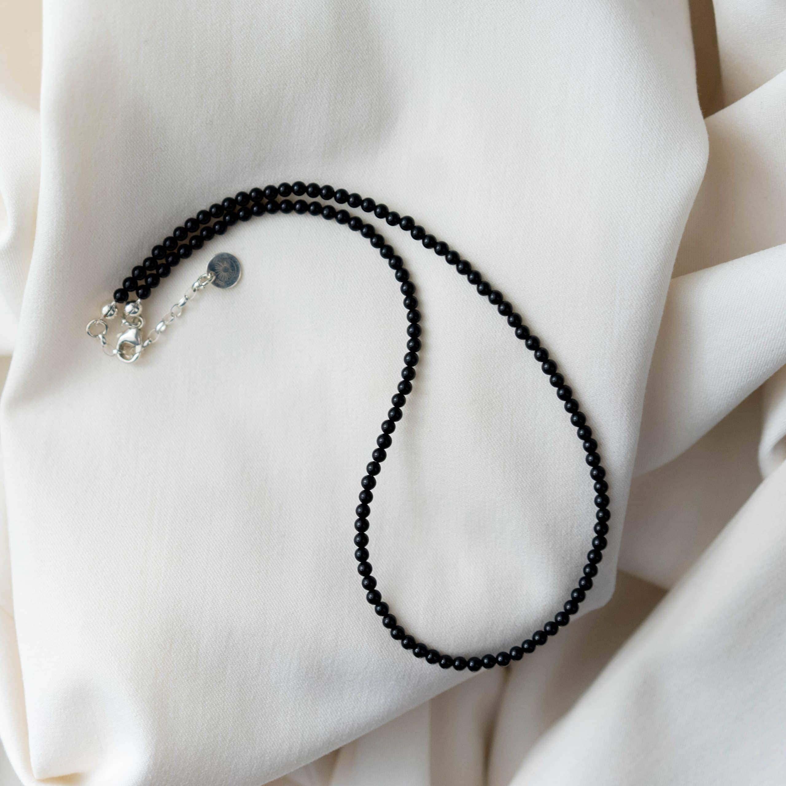 Czarny naszyjnik z drobnych kamieni na jasnym materiale,