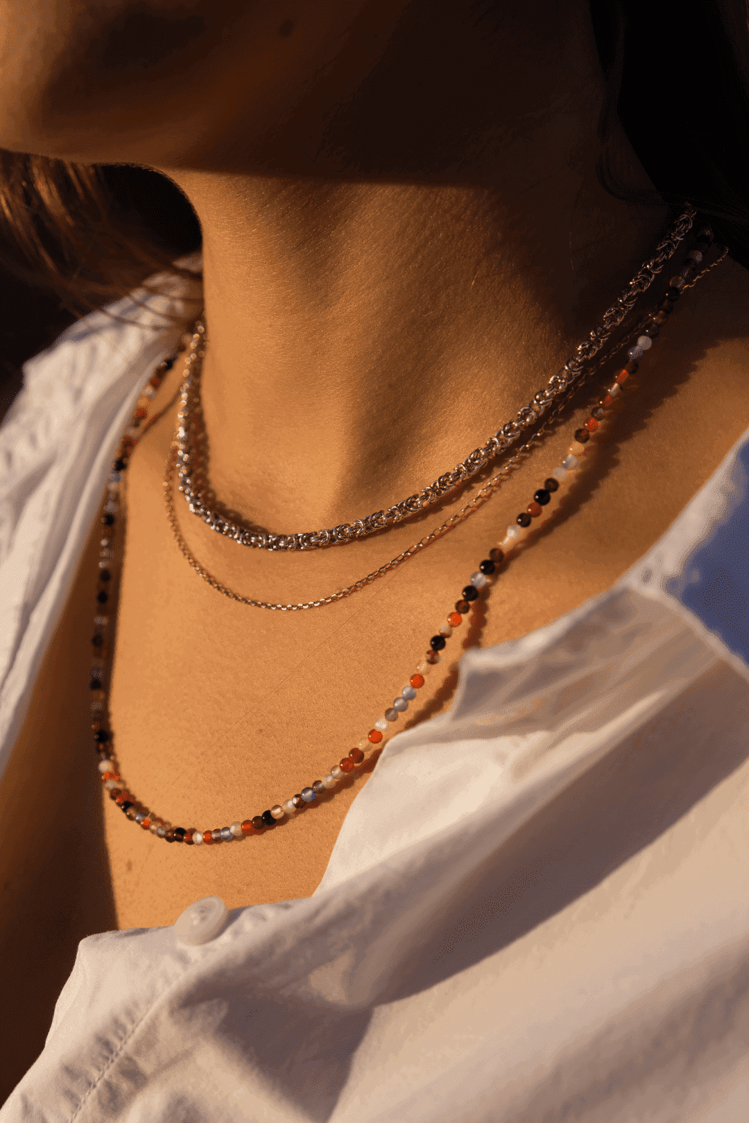 Modelka prezentuje na sobie zestaw naszyjników z kamienii kolorowych, złota i srebra