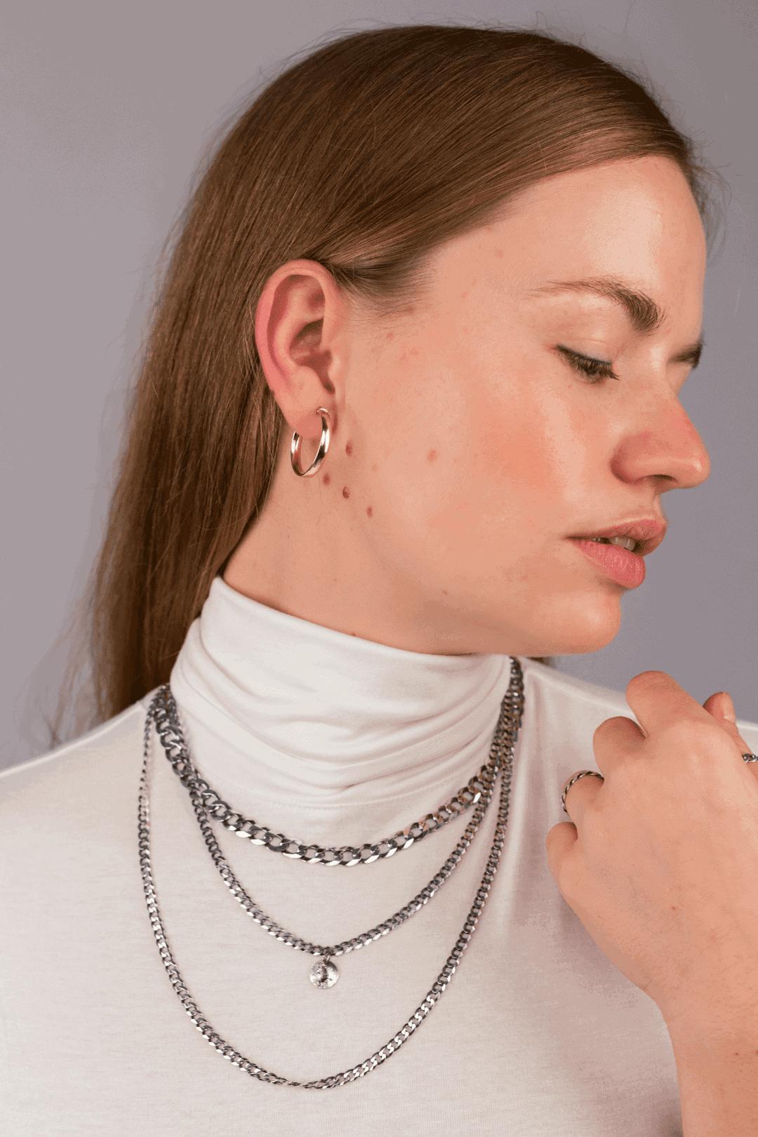 Modelka prezentuje zestaw masywnych, srebrnych naszyjników.