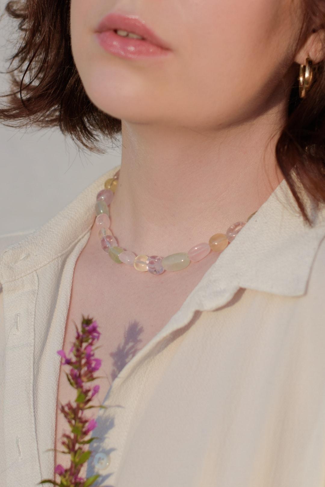 Modelka prezentuje na sobie naszyjnik z kolorowych kamieni z kwarcem różowym, górskim i cytrynami.