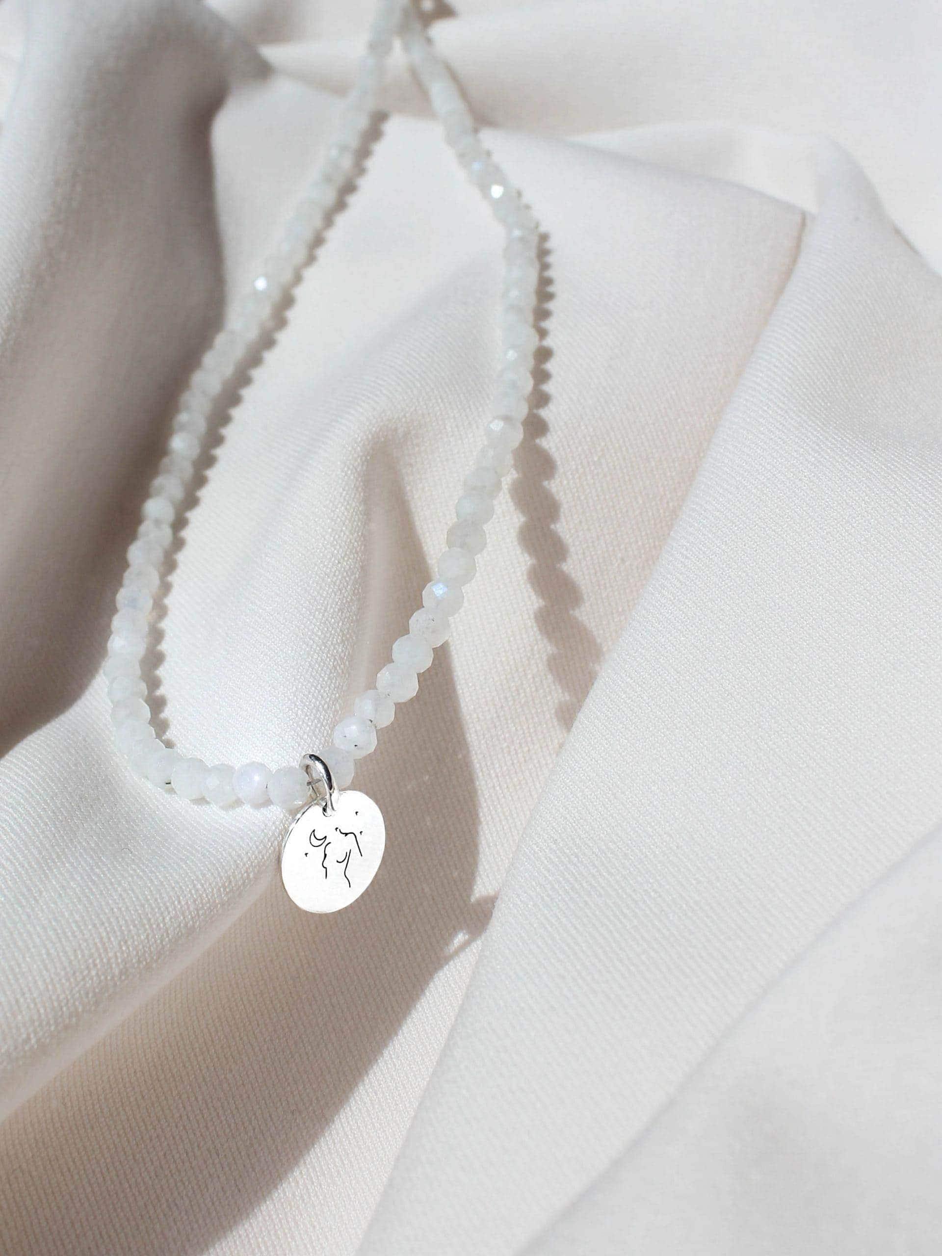 Biały naszyjnik z drobnych kamieni naturalnych ze srebrną zawieszką i grawerem kobiecego ciała