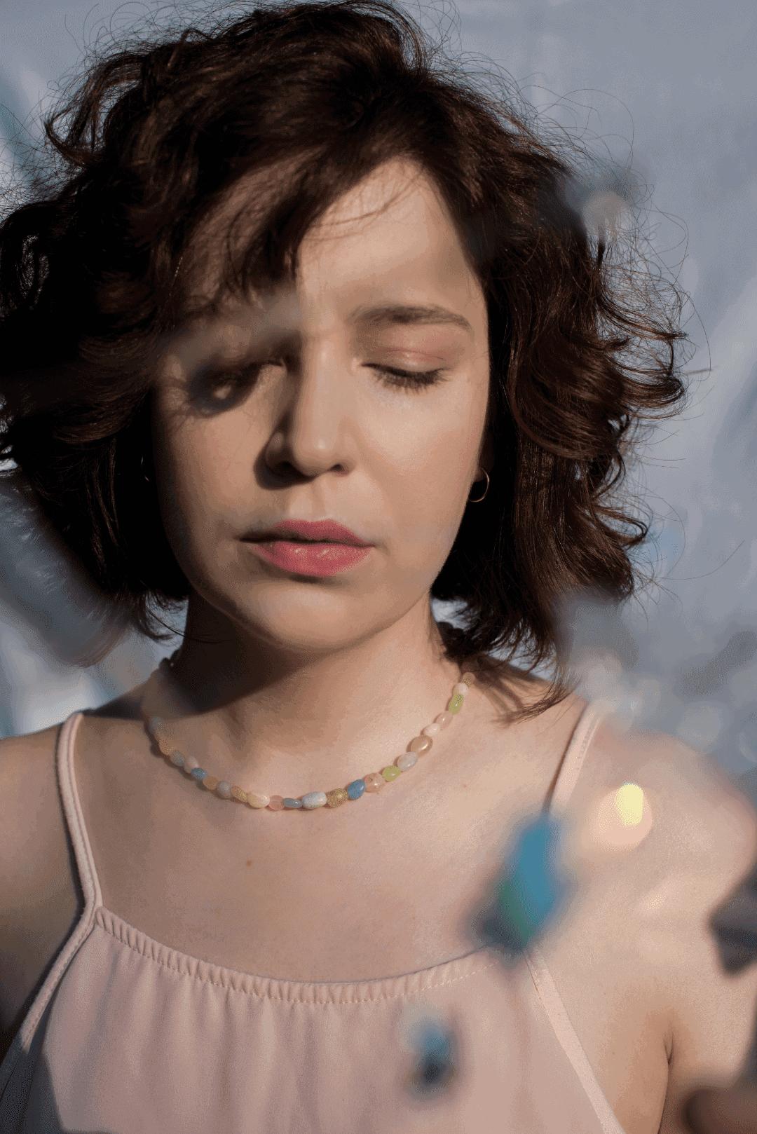 Modelka prezentuje na sobie naszyjnik z kolorowych kamieni: naturalnych morganitów.