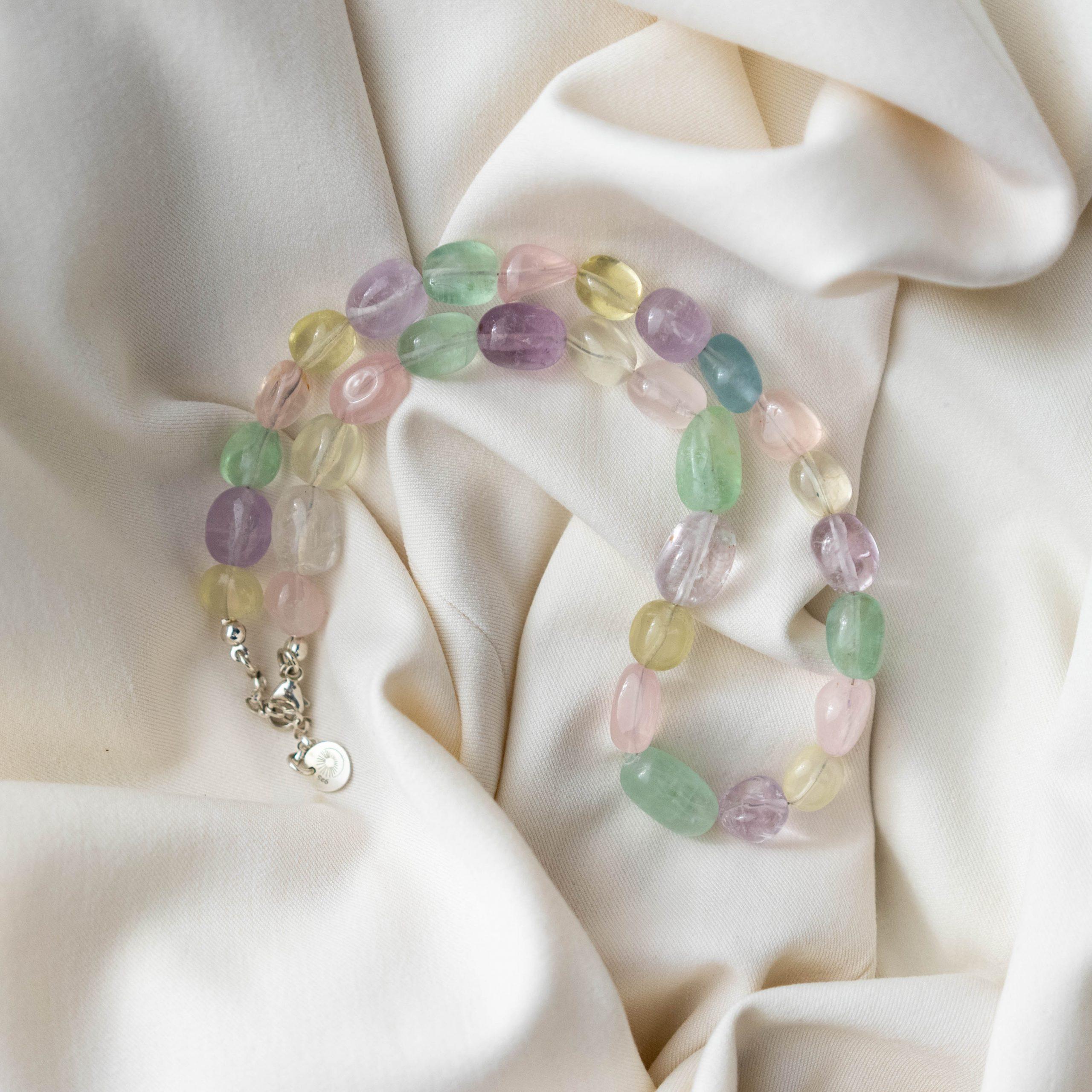 Naszyjnik z kolorowych kamieni szlachetnych: różowych, zielonych i żółtych na jasnym materiale.