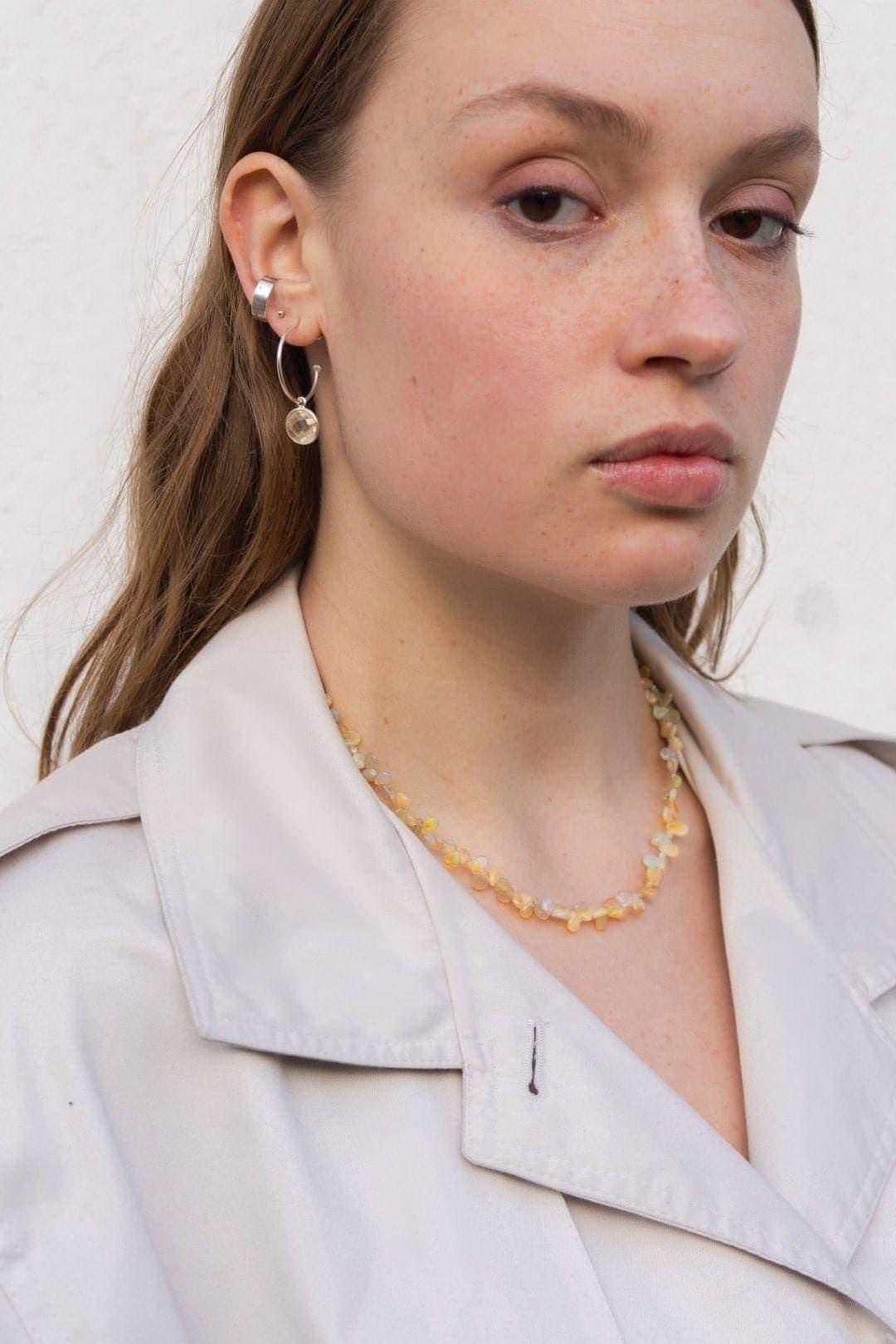 Modelka prezentuje połyskujący naszyjnik z opali i kolczyki koła z zawieszką oraz srebrną nausznice