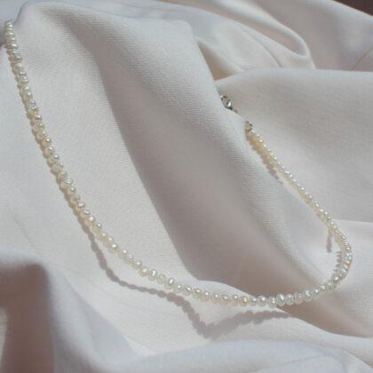 Naszyjnik z drobnych preł na jasnym materiale