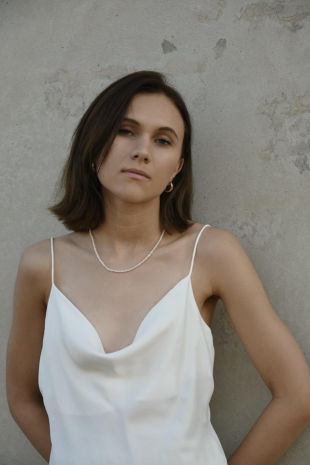 Modelka prezentuje naszyjnik z pereł naturalnych.