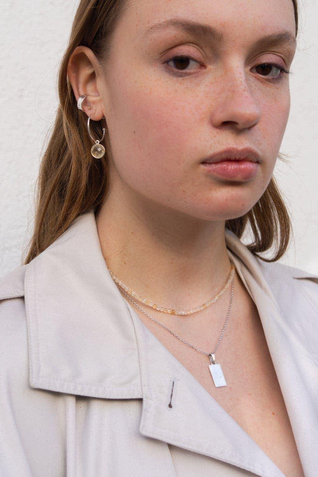 Modelka prezentuje na sobie srebrny naszyjnik z grawerem, żółty naszyjnik z cytrynem i kolczyki koła z zawieszką.