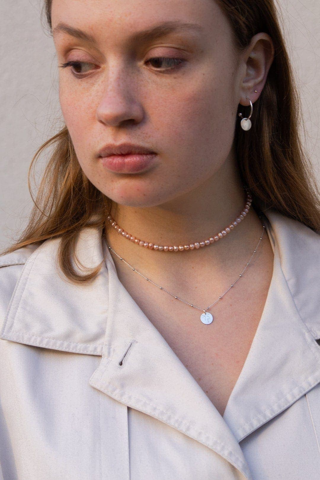 Modelka prezentuje komplet biżuterii z pereł, naszyjnik z zawieszką grawer i kolczyki koła z zawieszką