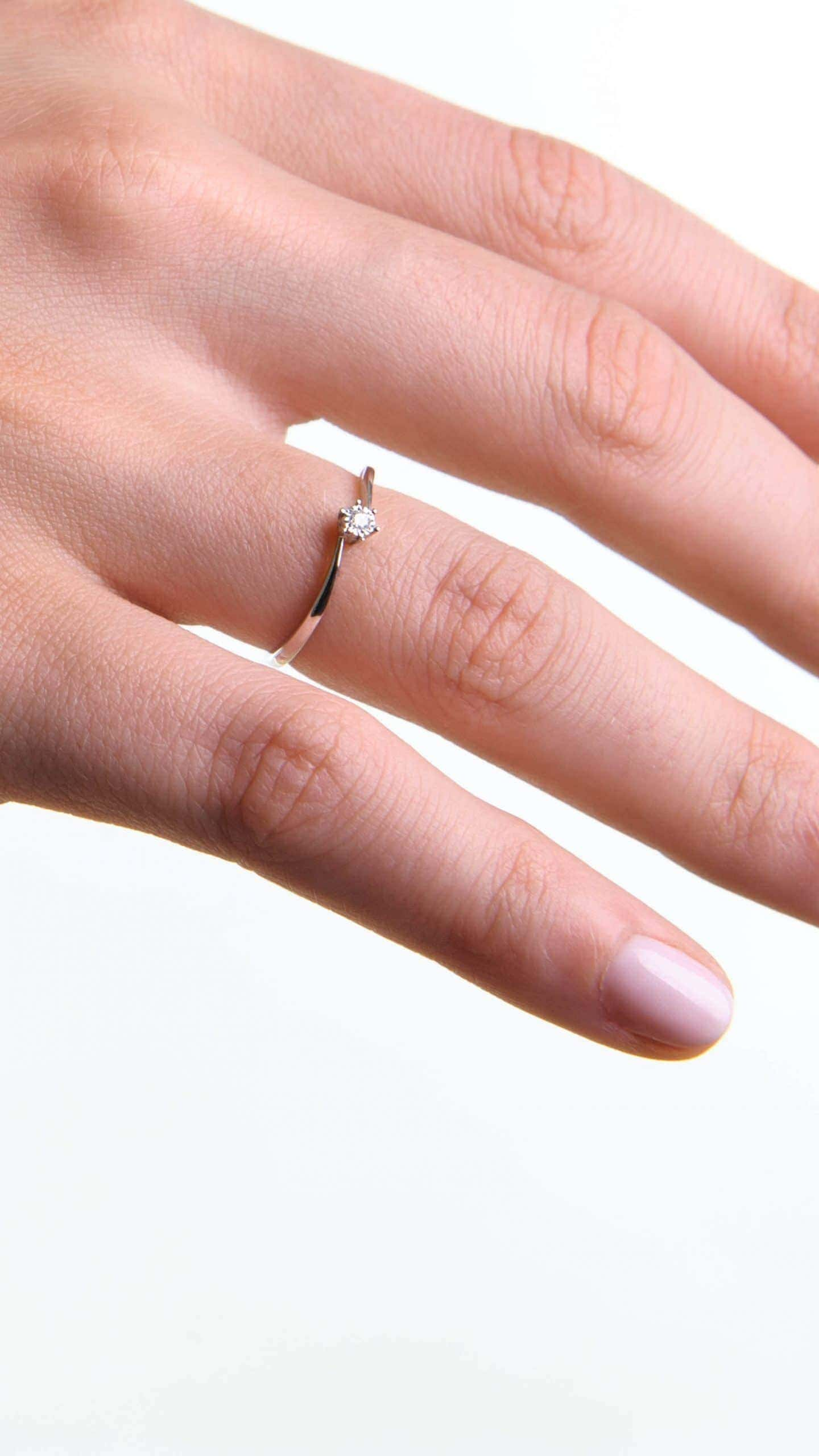 Modelka prezentuje na dłoni zaręczynowy pierścionek z białego złota z diamentem.
